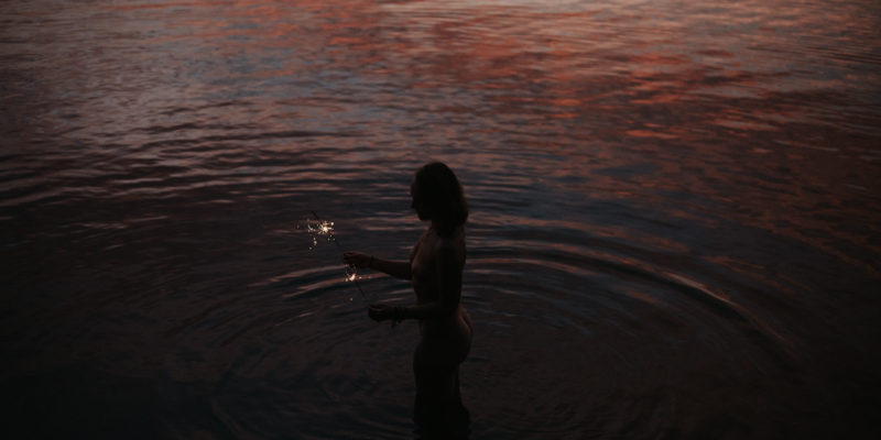 Naked woman in the water with sparklers at sunset // Photo by: Daring Wanderer www.daringwanderer.com