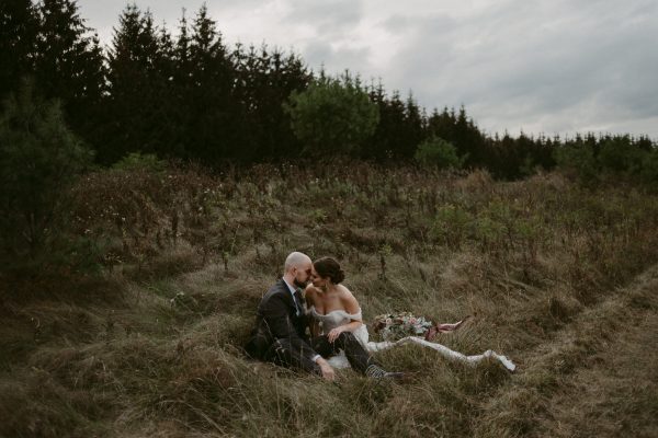 wedding couple sitting in field after ceremony