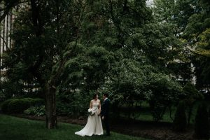 Couple walking in front of Osgoode Hall on their wedding day