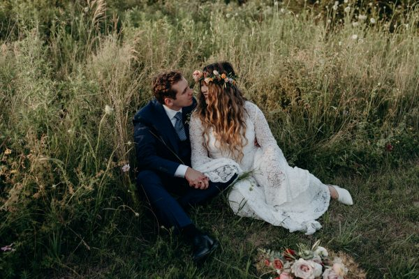 couple sitting in tall grass on wedding day at sunset