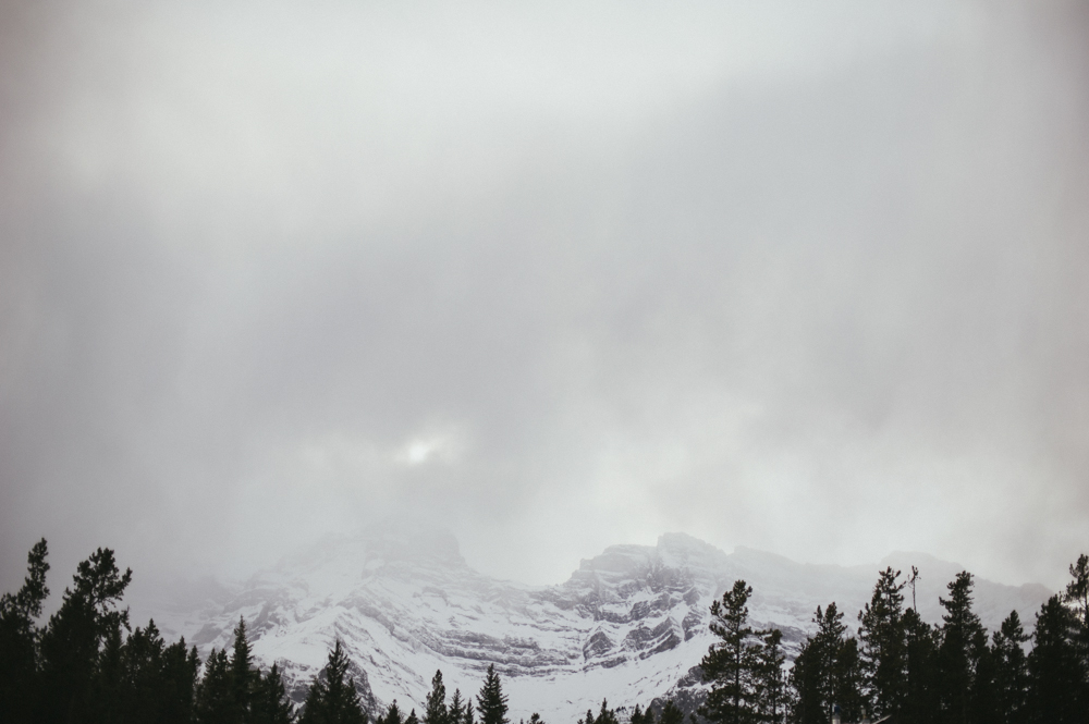 Sun poking through the clouds atop a mountain in Banff