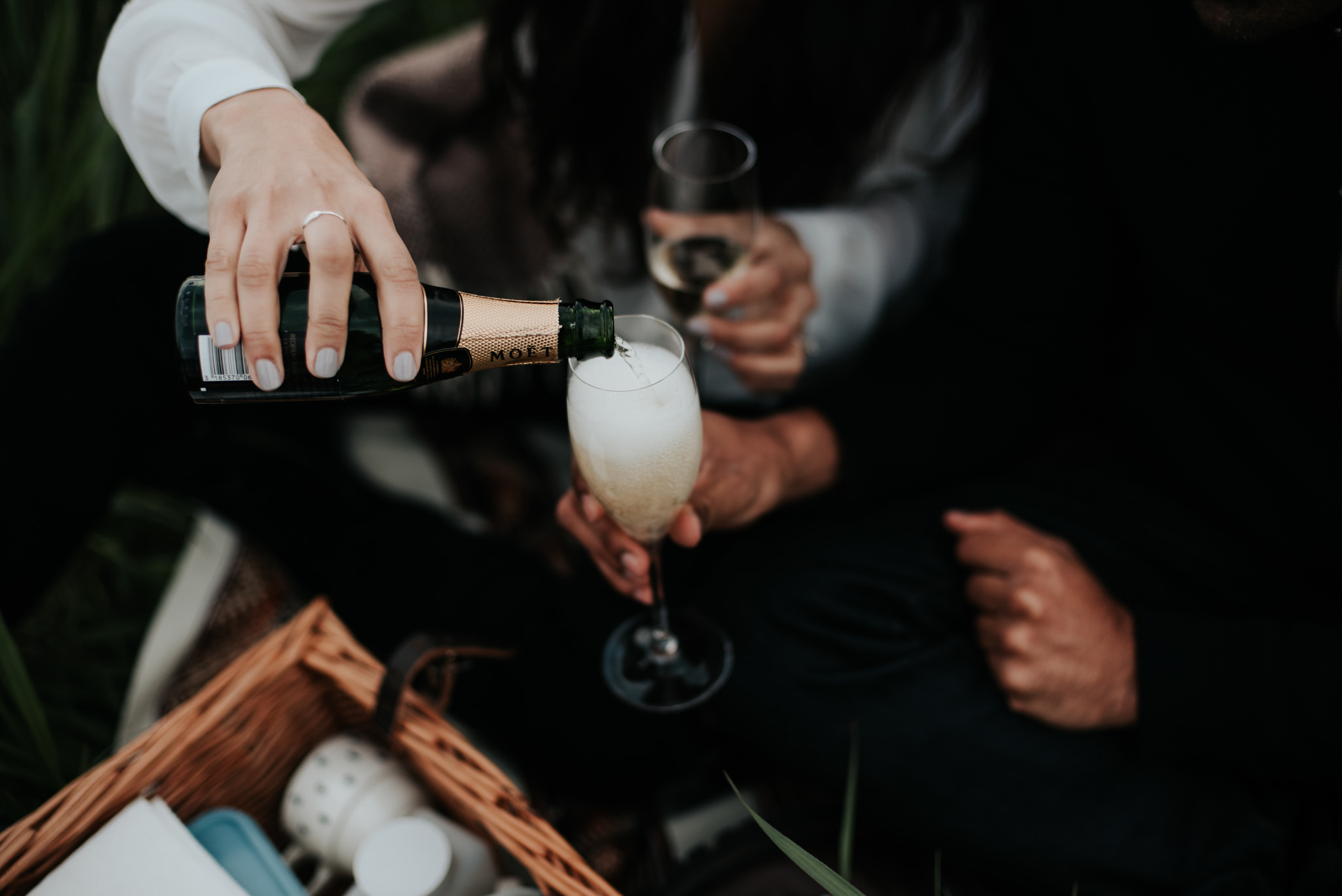Couple pouring champagne into glasses at picnic