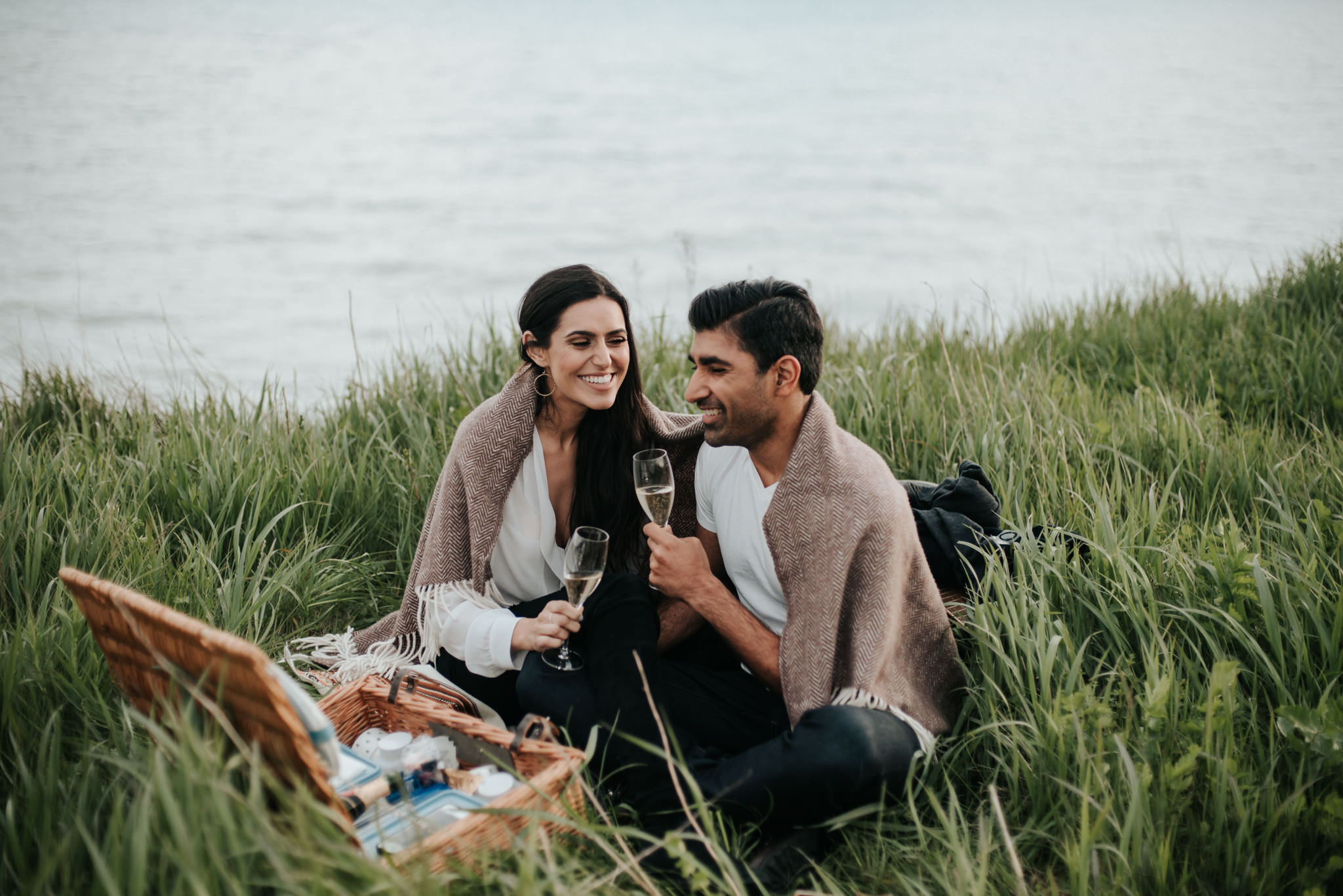 Young couple laughing and smiling in field with picnic setup for engagement