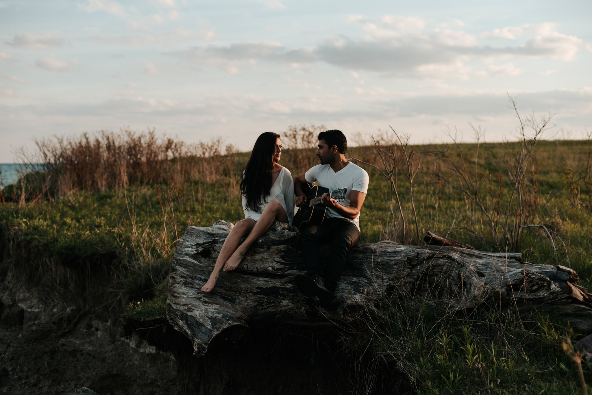 Young couple sitting on log on cliff by water playing guitar