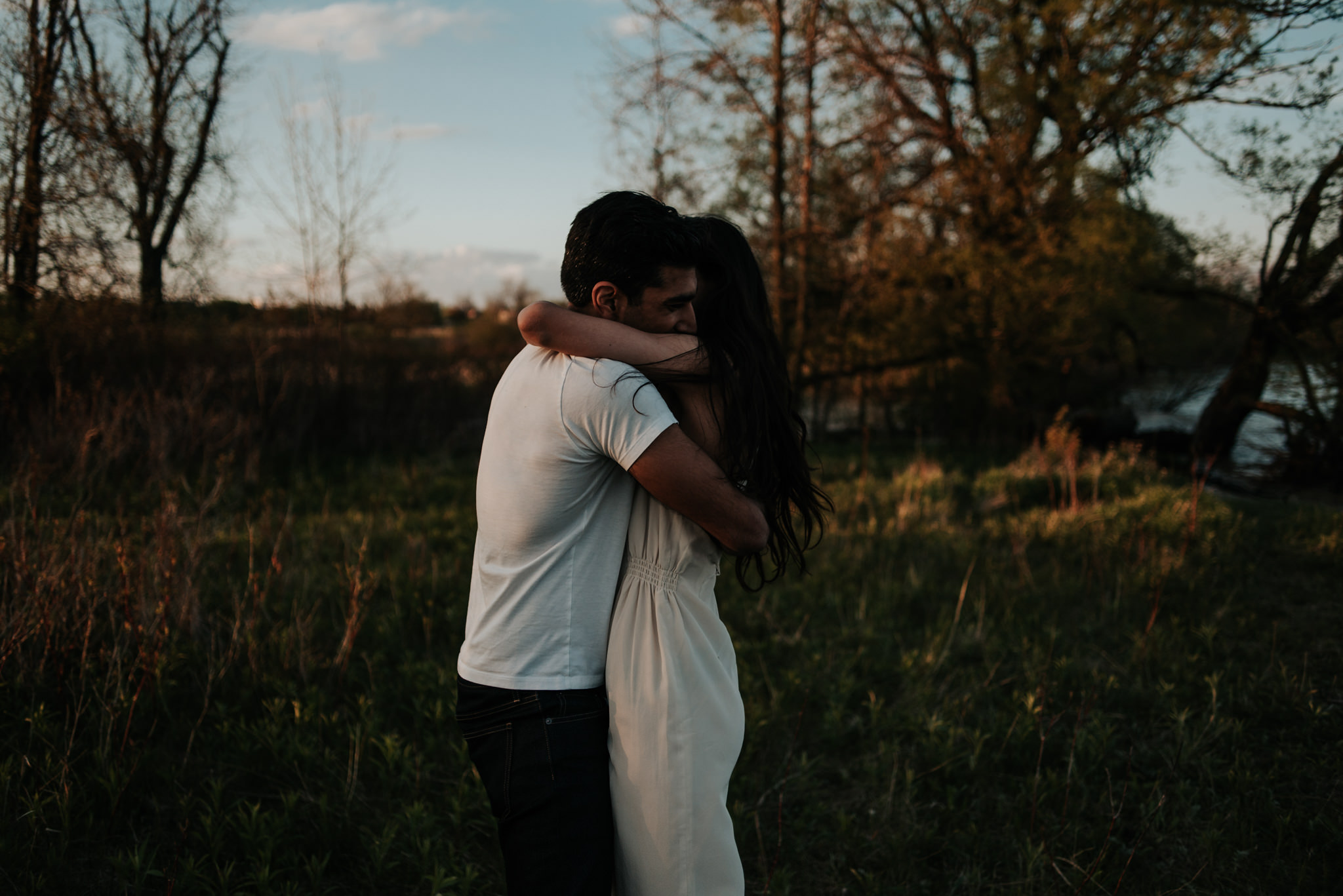 Dreamy wanderlust couple hugging at dusk, woman in white dress