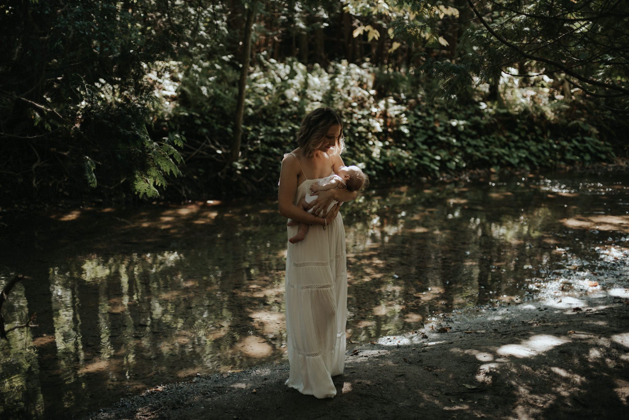 New mother carrying newborn daughter by a river in a forest for newborn portraits