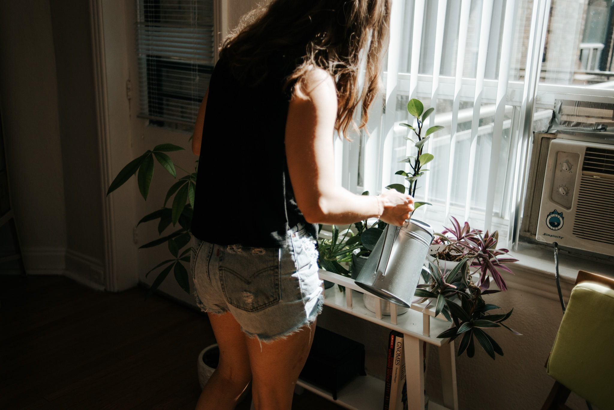 Girl watering plants by window inside apartment