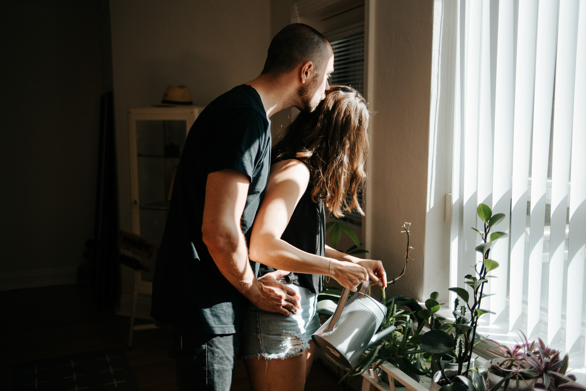 Guy hugging girl from behind as she waters plants in apartment