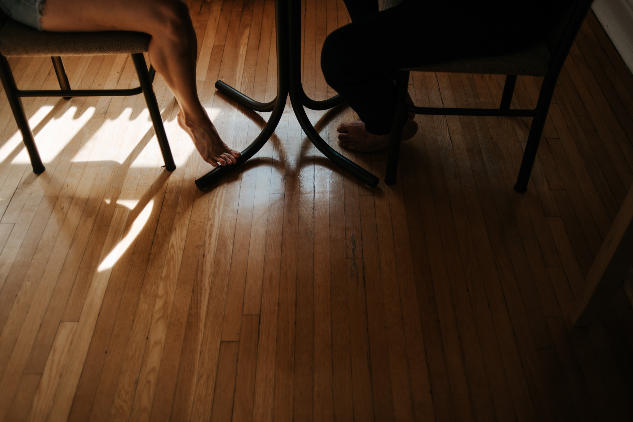 Couple feet while sitting at table in apartment