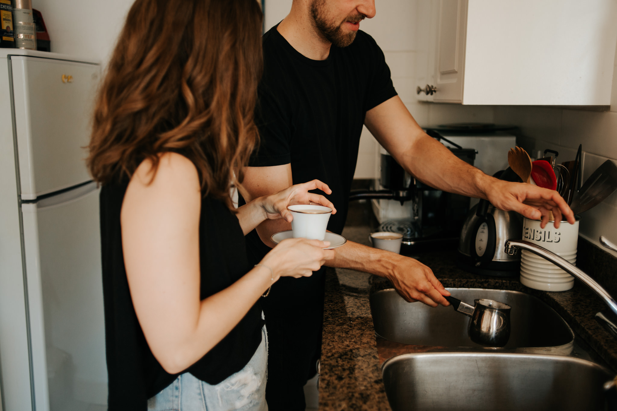 Couple making coffee in apartment kitchen