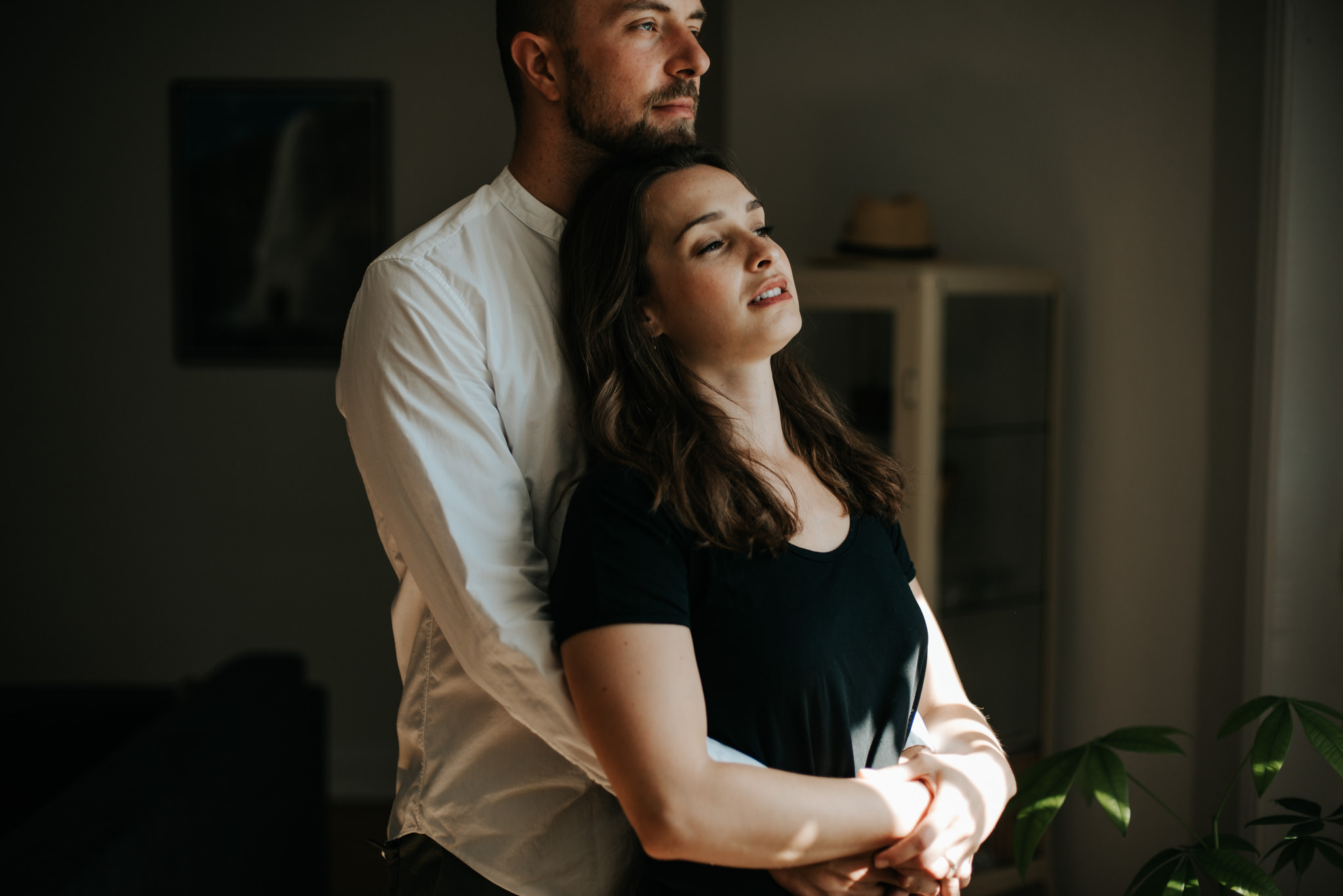 Intimate moment between young couple as they hug by window in living room