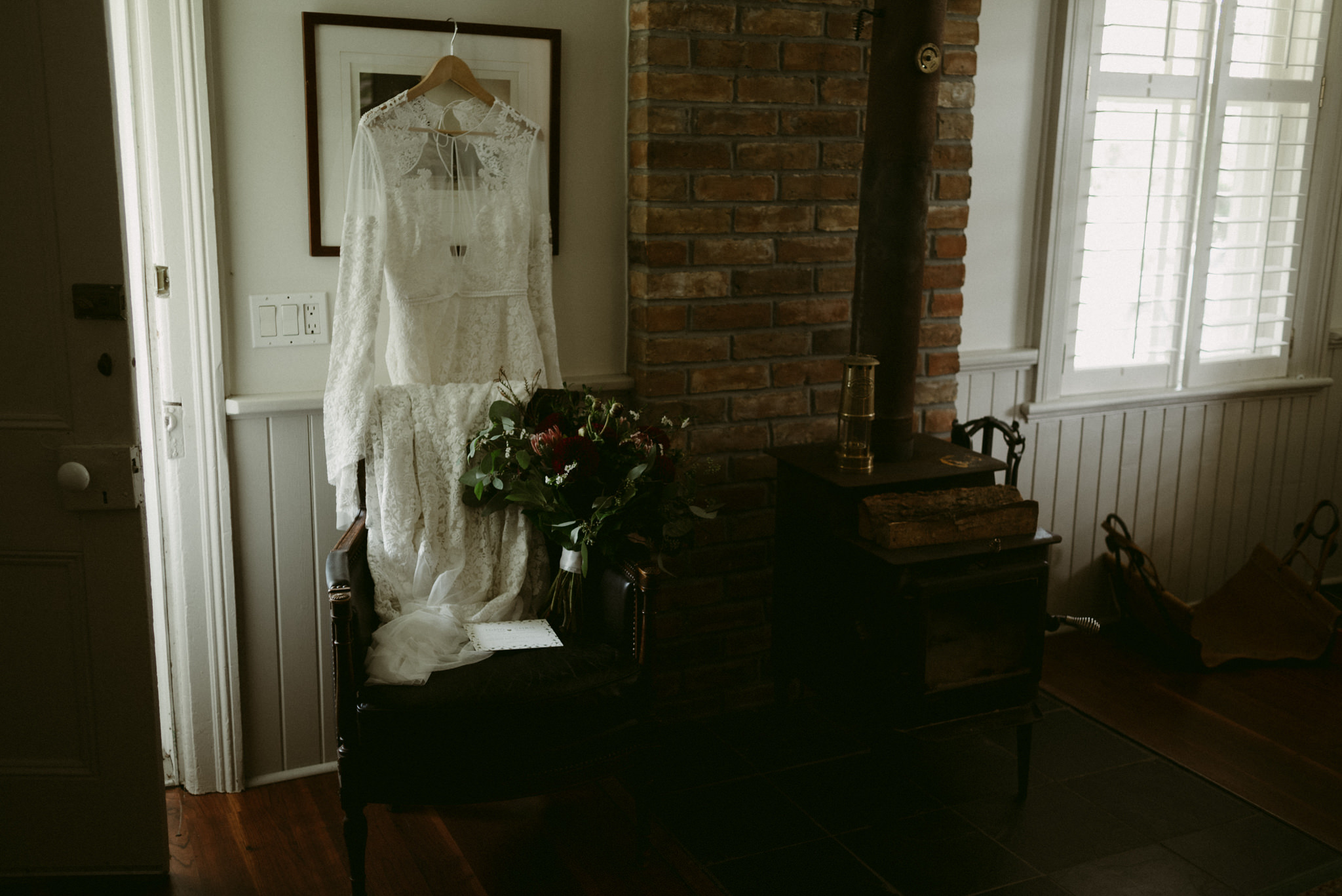 Lace Rue de Seine wedding dress hanging inside farm house