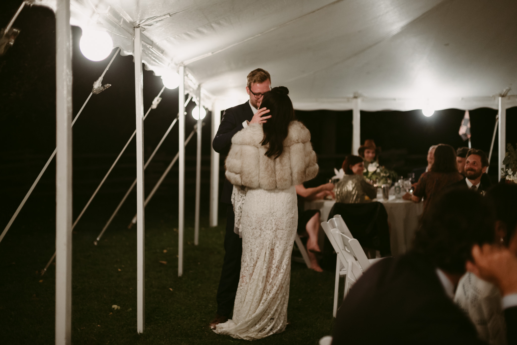 Bride and groom kissing in tent at wedding reception