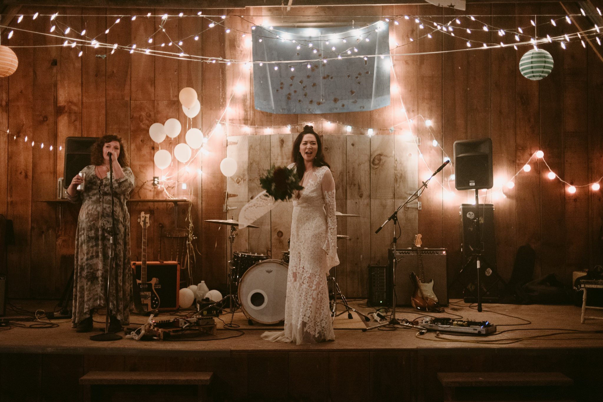 bride on stage with string lights and balloons