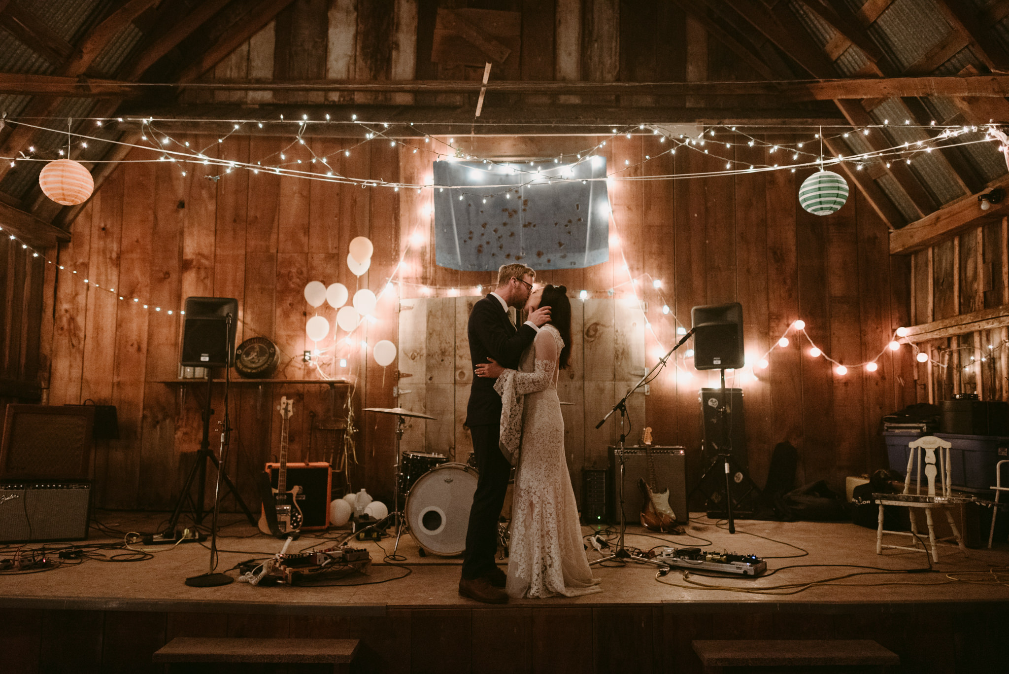 bride and groom kissing in barn during wedding reception