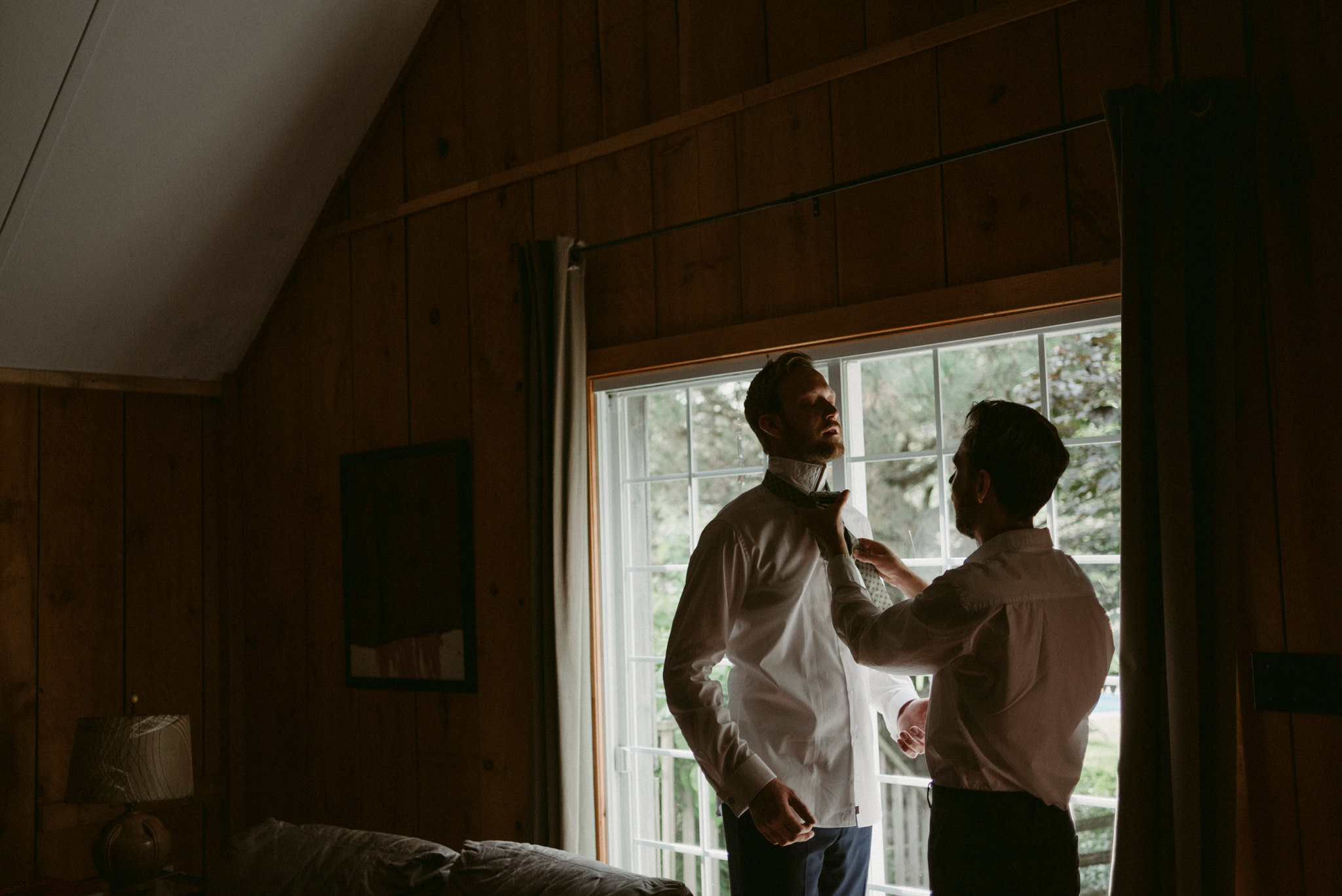 Best man tying groom's tie in cabin