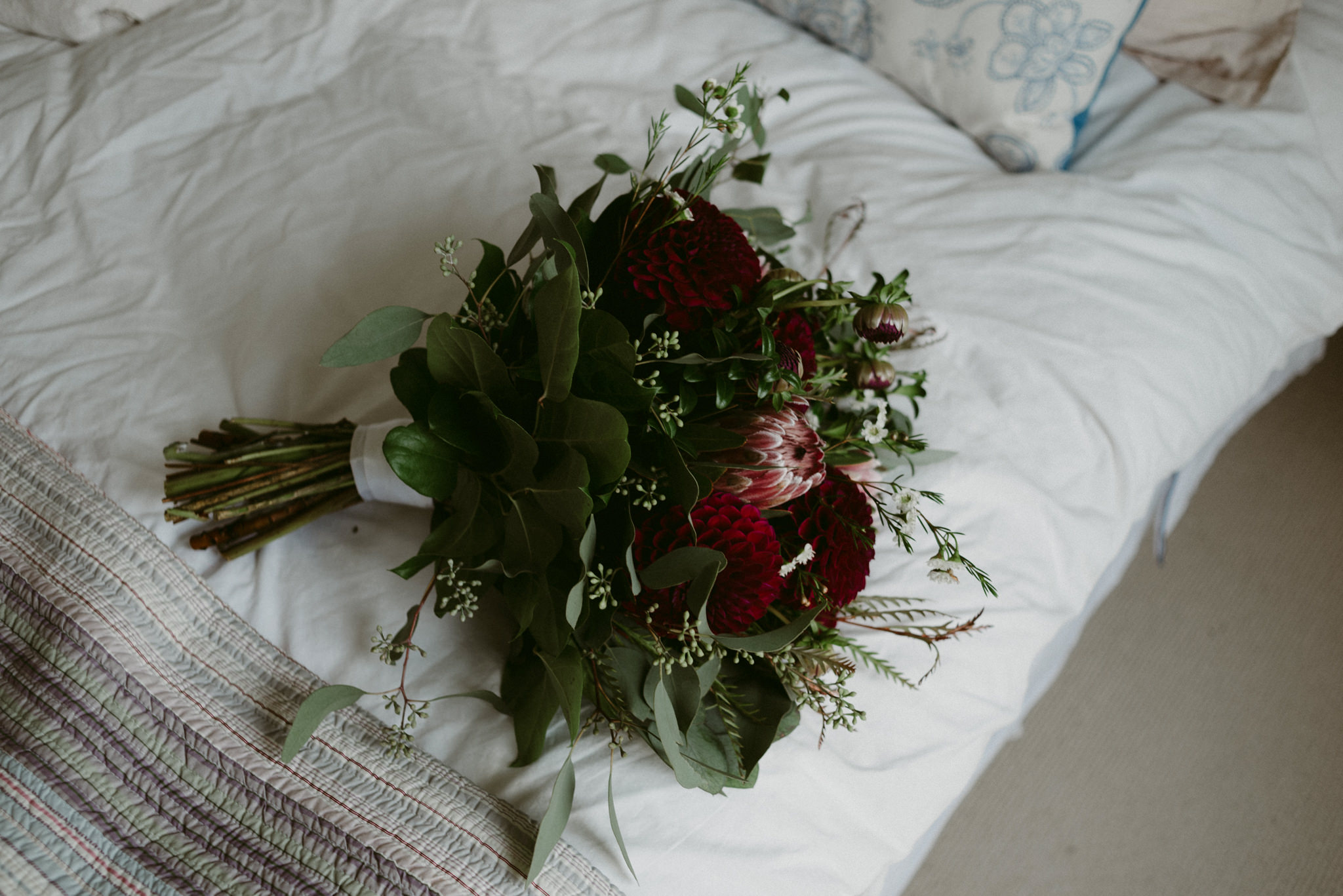 Green and maroon wedding bouquet on bed