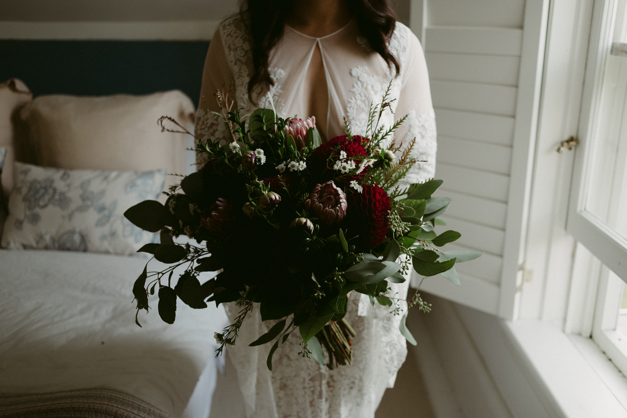 Bride in lace dress holding maroon and dark green bouquet