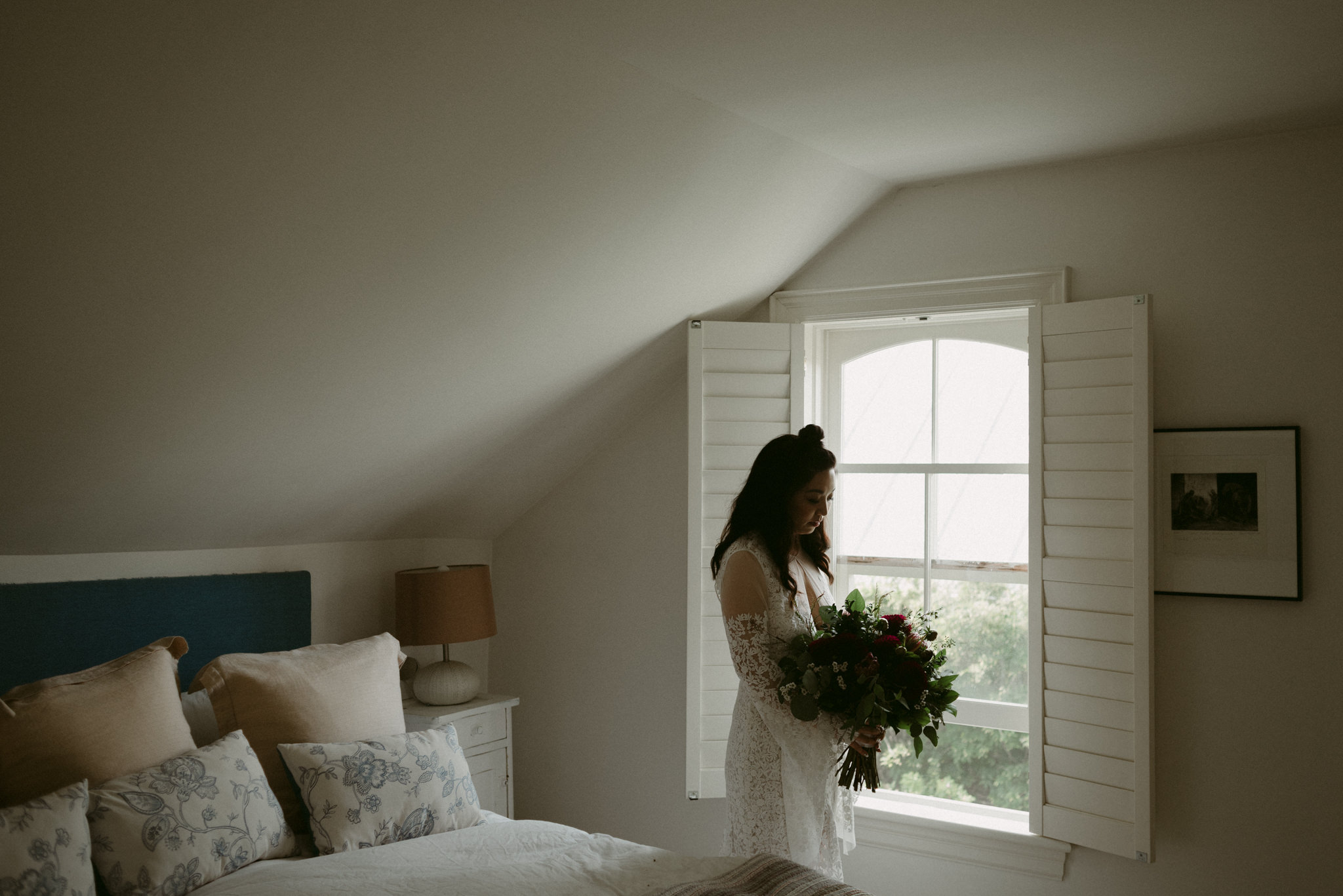 Bride in lace dress holding wedding bouquet by window