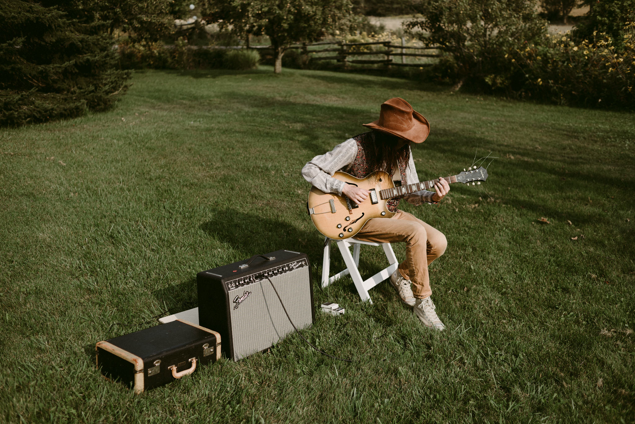 Hipster musician playing guitar at outdoor backyard wedding ceremony
