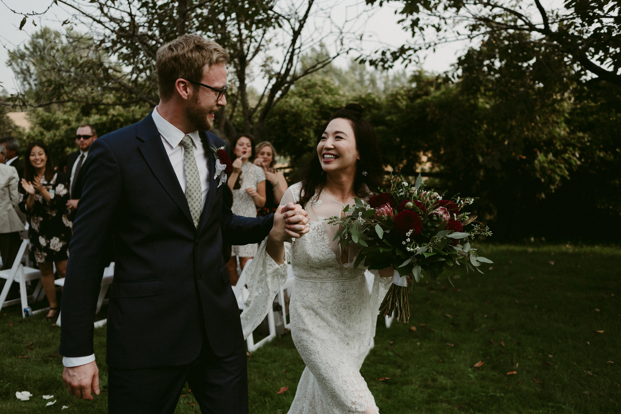 bride smiling at groom walking down aisle after outdoor backyard wedding ceremony
