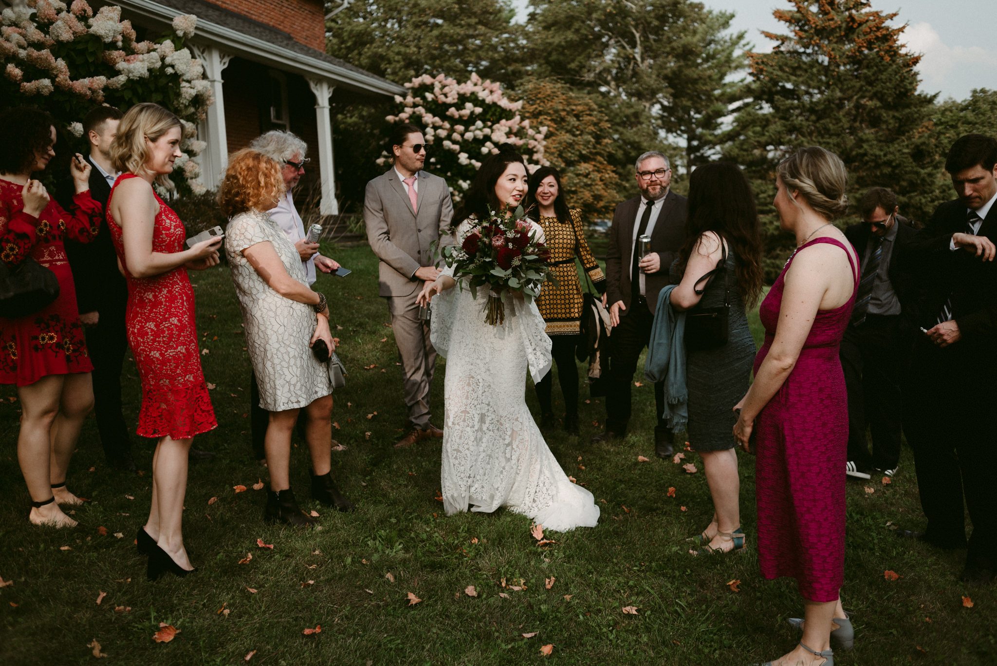 bride with guests outside farm house