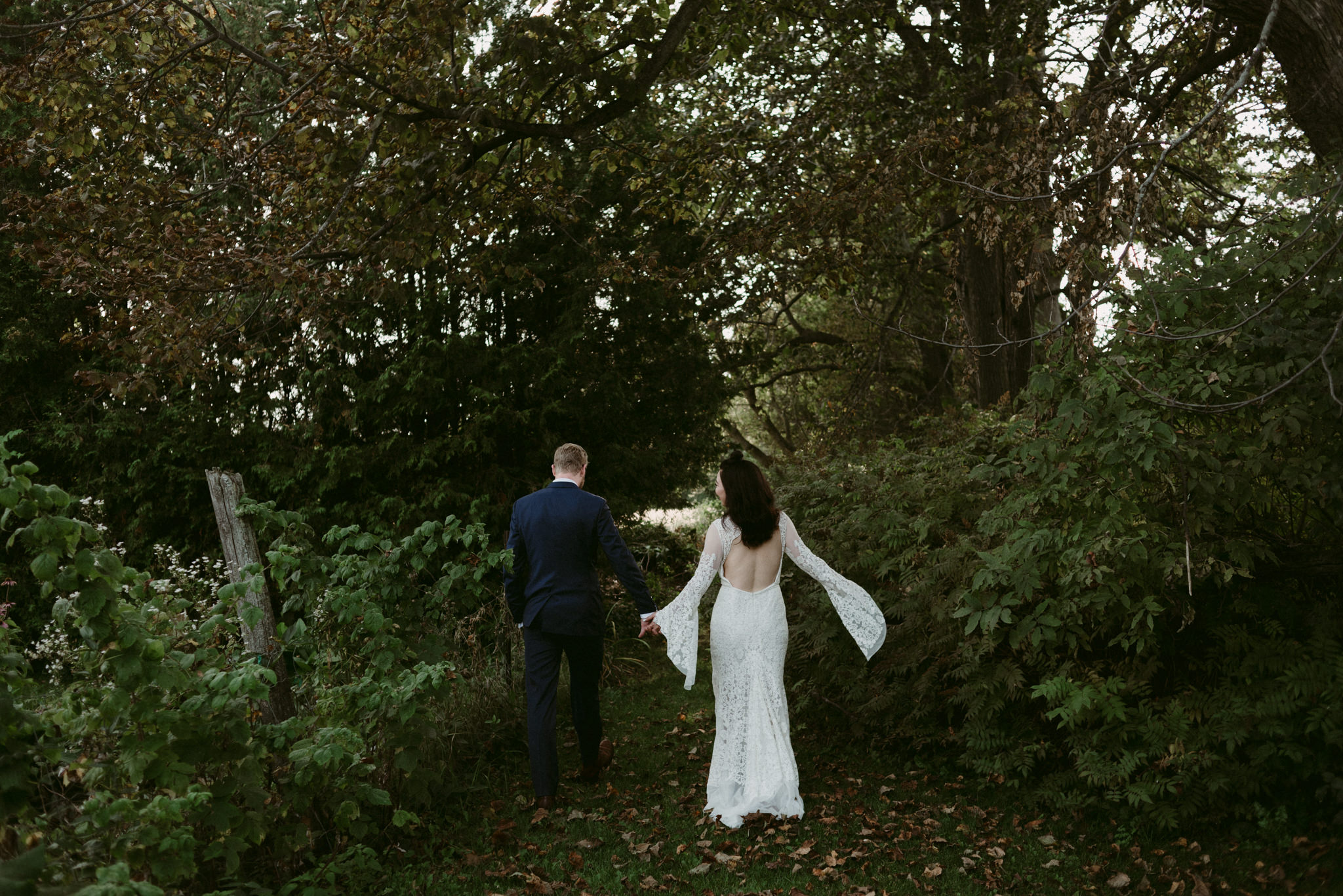 bride and groom walking into forest