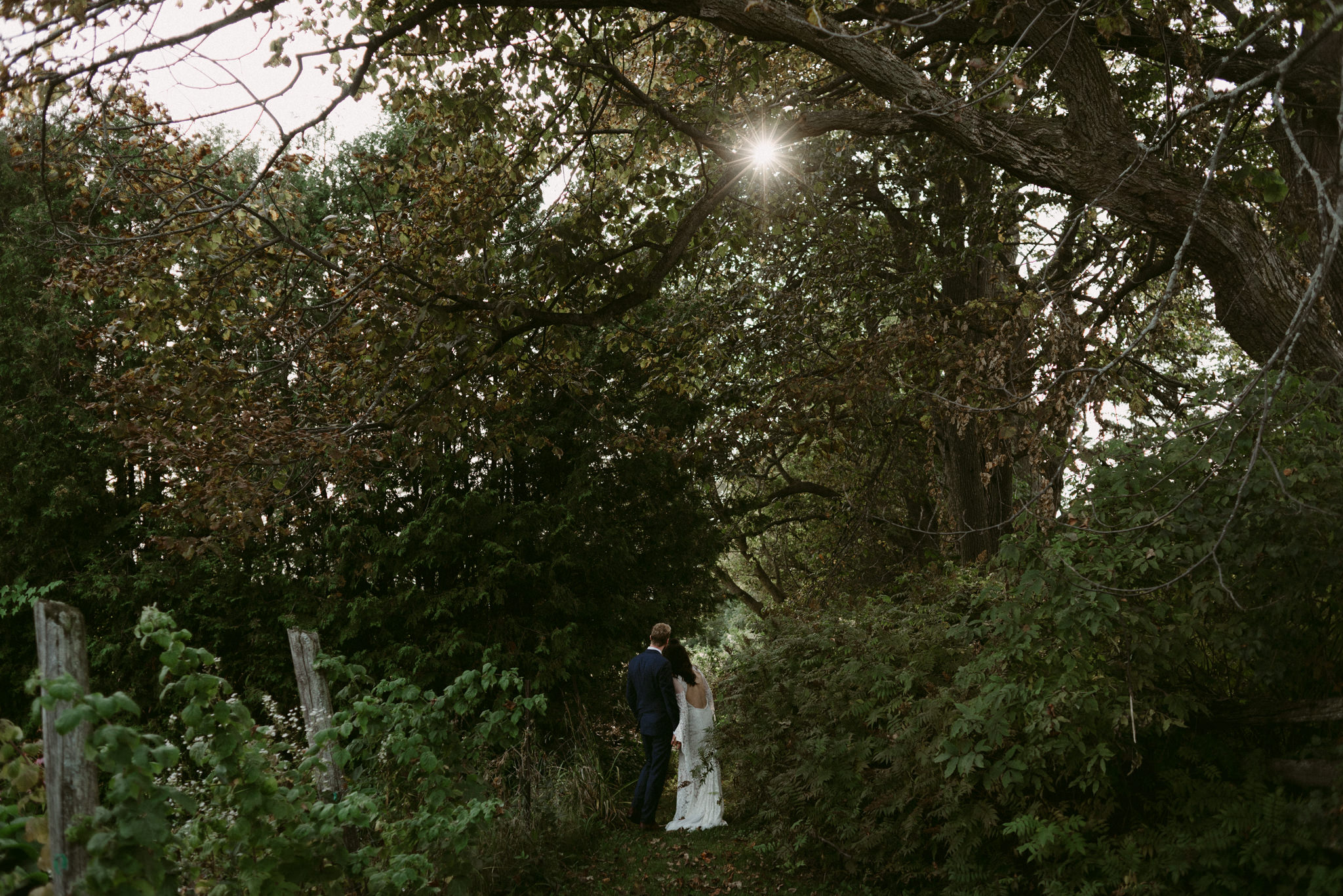 Bride and groom standing in lush garden with sun beaming through leaves