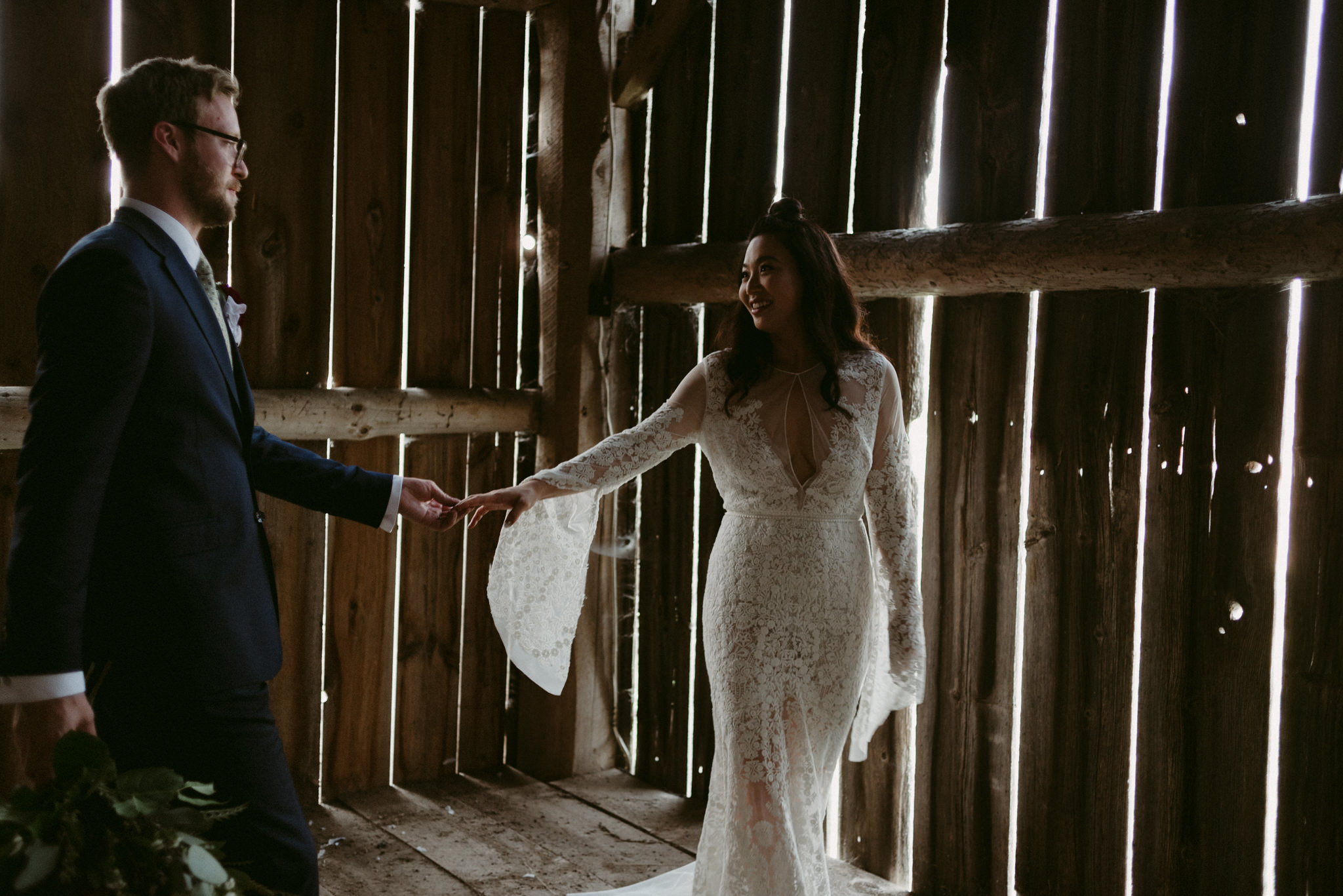 bride and groom holding hands in barn