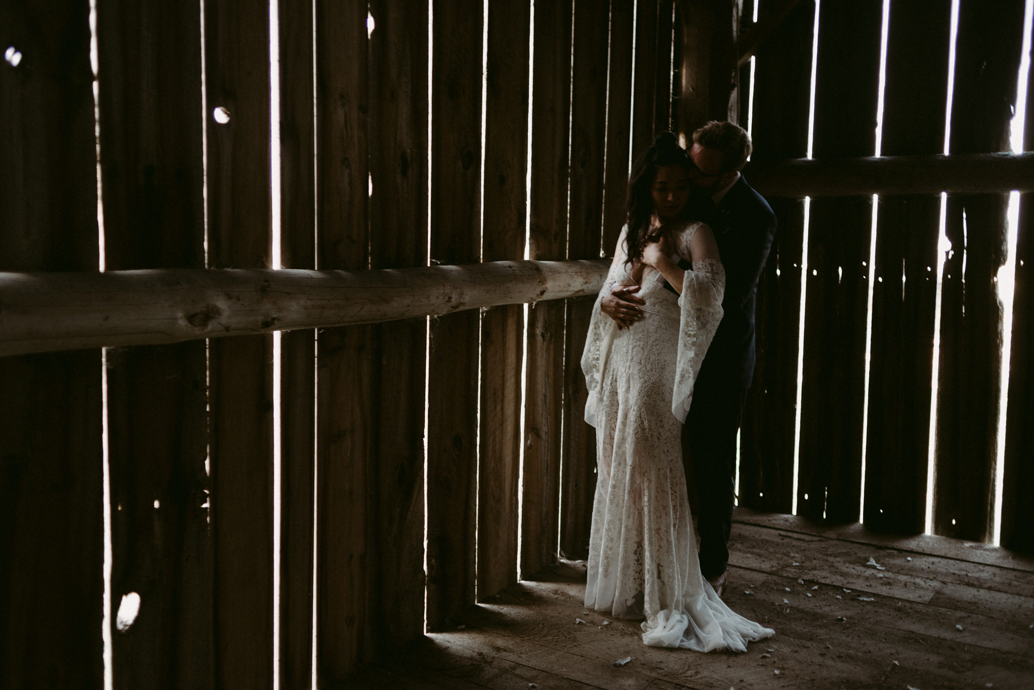 groom hugging bride from behind in barn