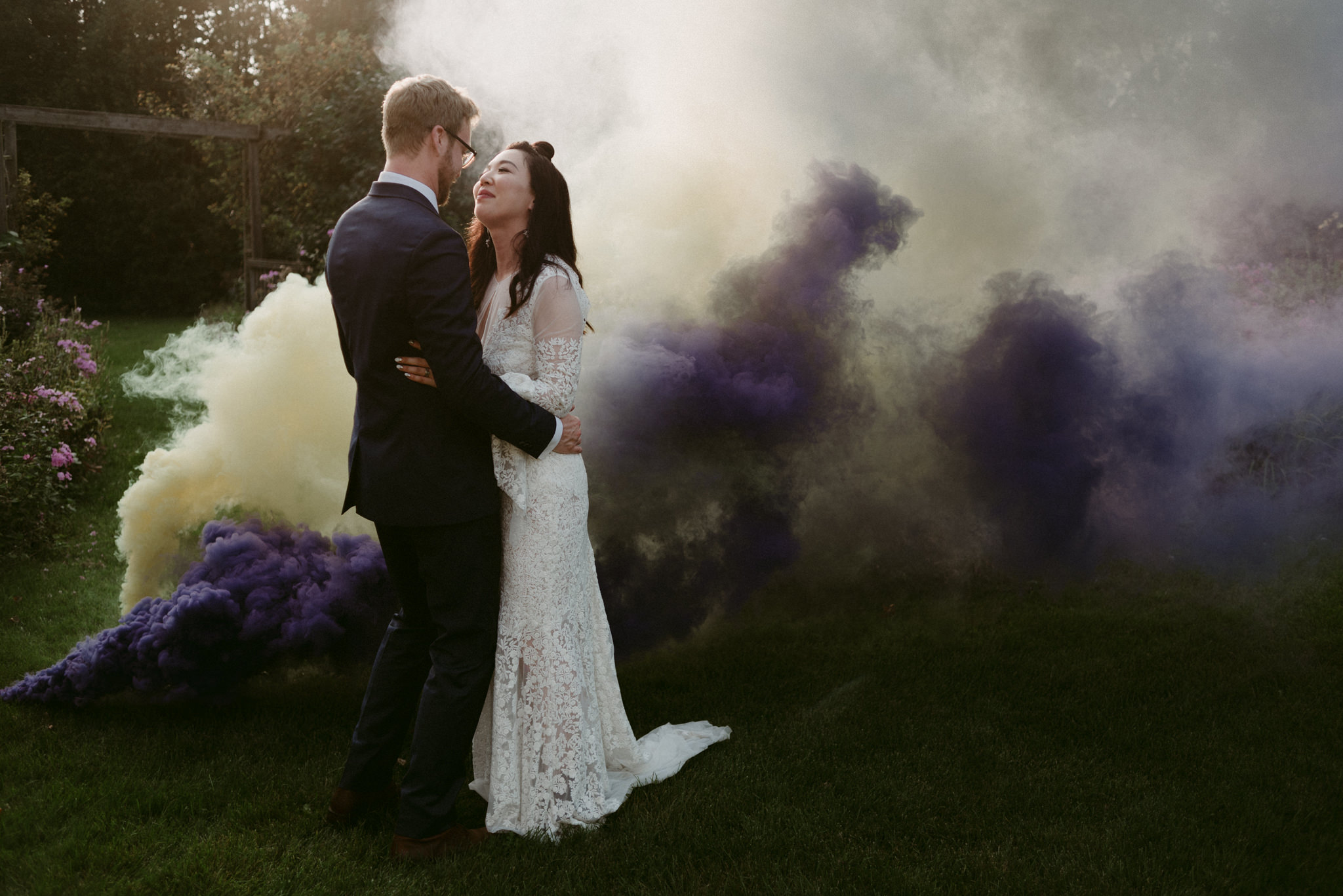 bride and groom kissing with smoke bombs around them