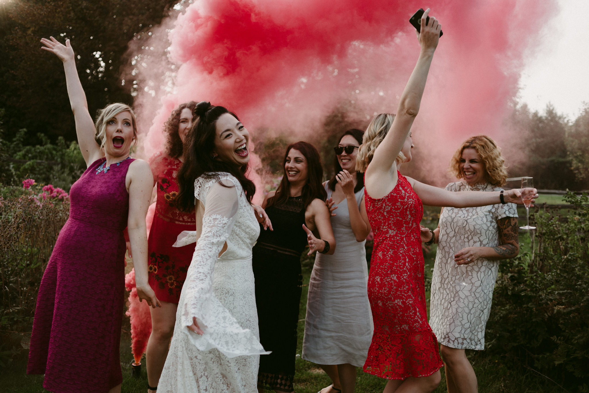 bride with friends laughing in red smoke bomb