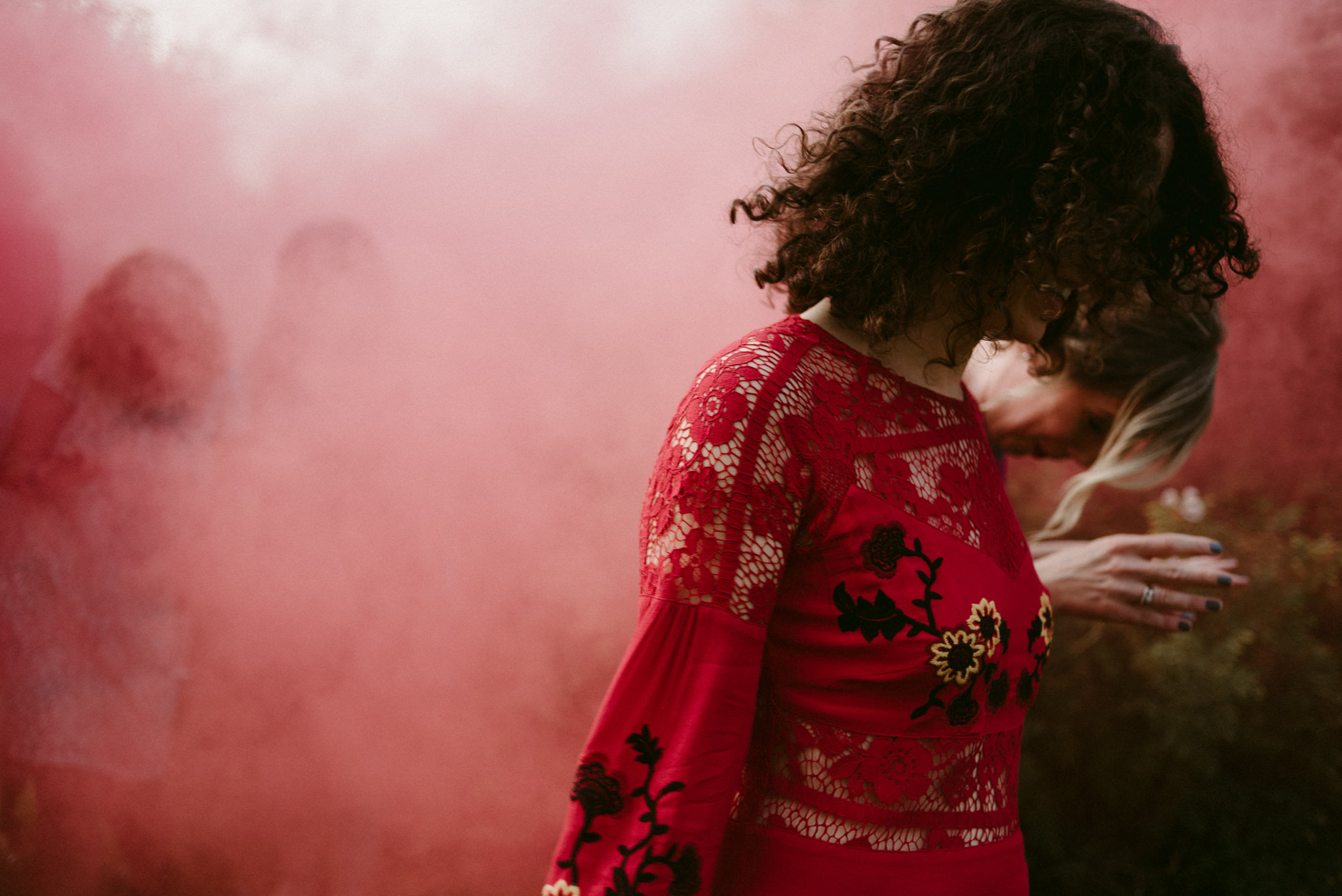 guest running through red smoke bomb at wedding reception