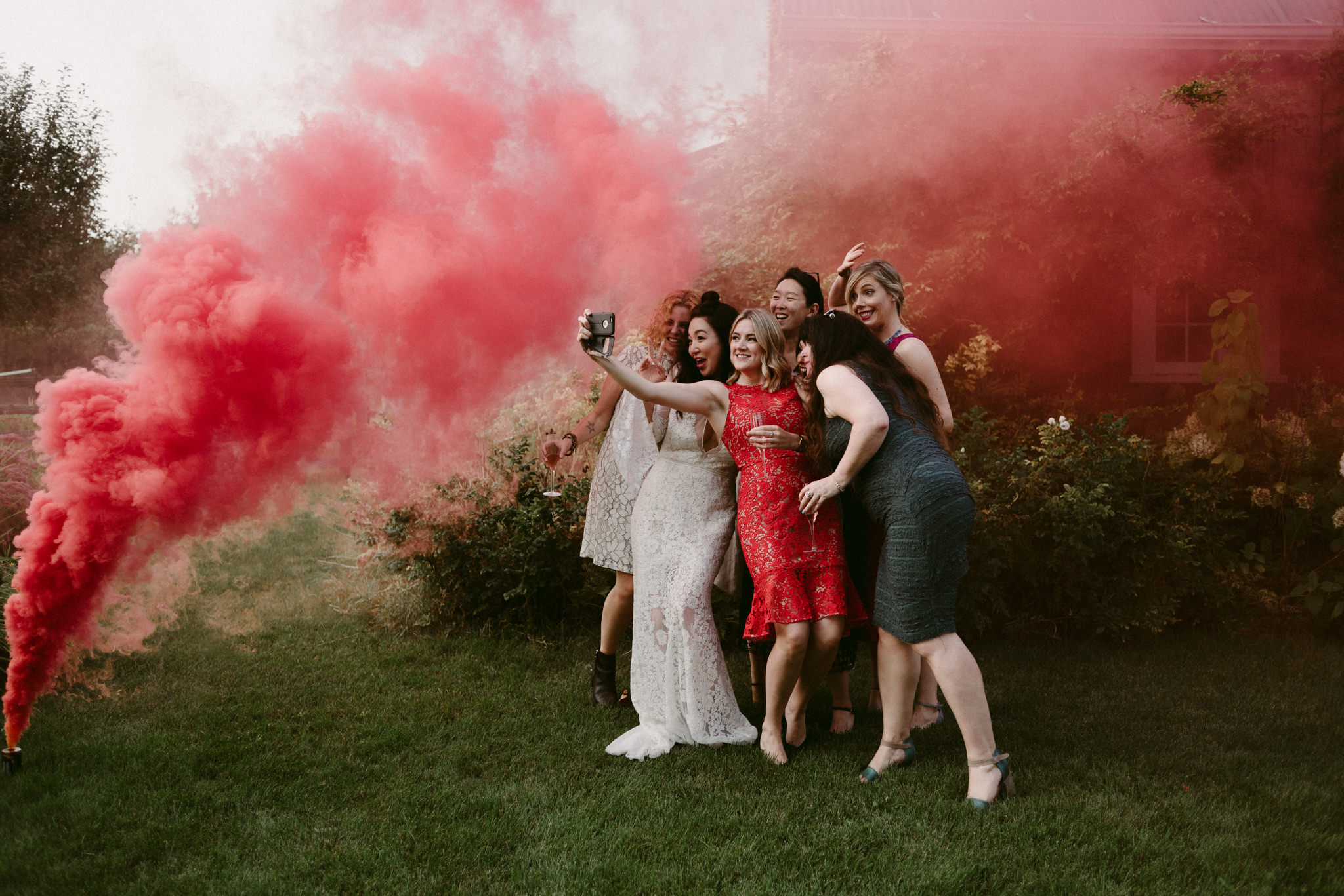 bride with friends taking selfie in red smoke bomb