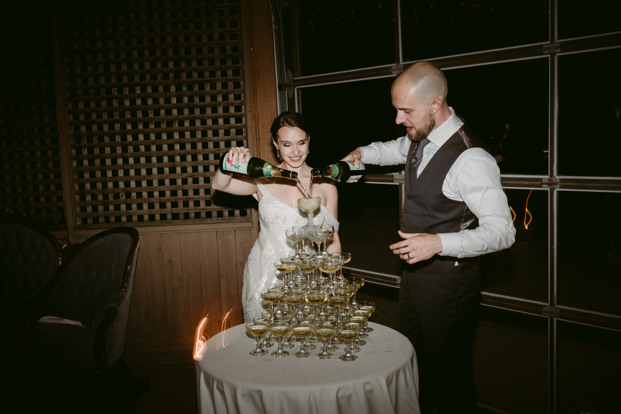 Bride and groom pouring champagne on champagne tower