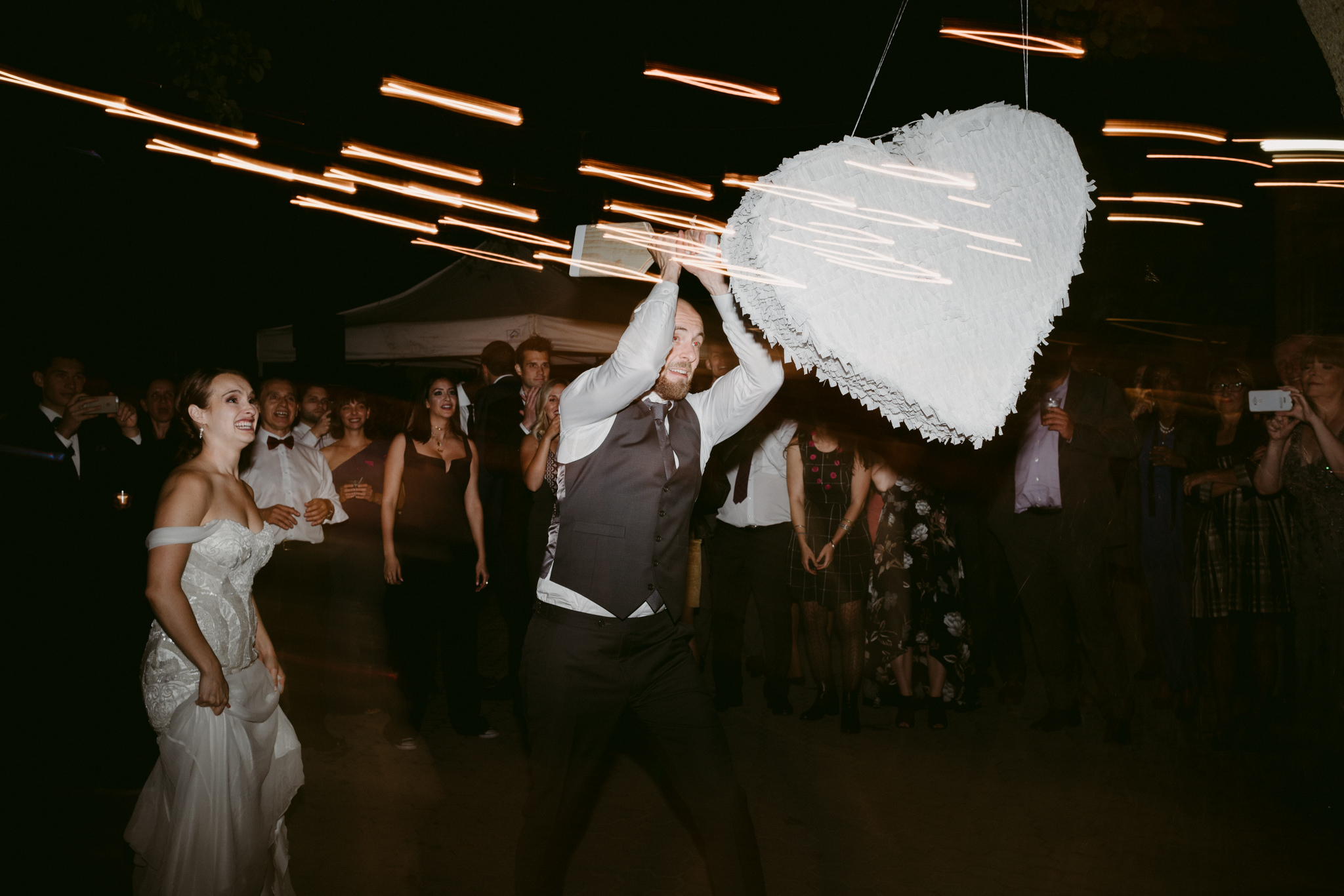 Groom hitting piñata at wedding