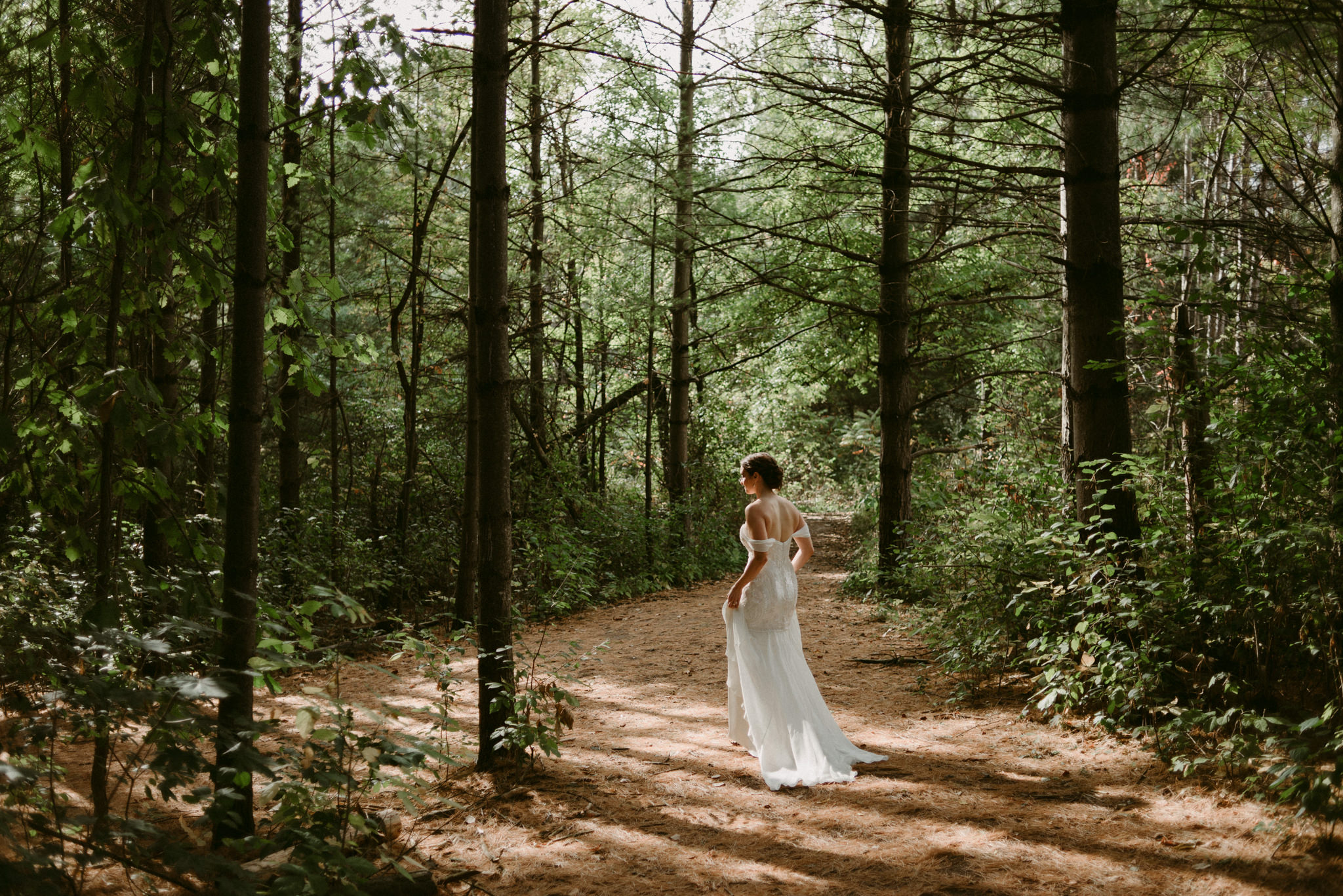 Bride walking in forest at Kortright Centre for Conservation