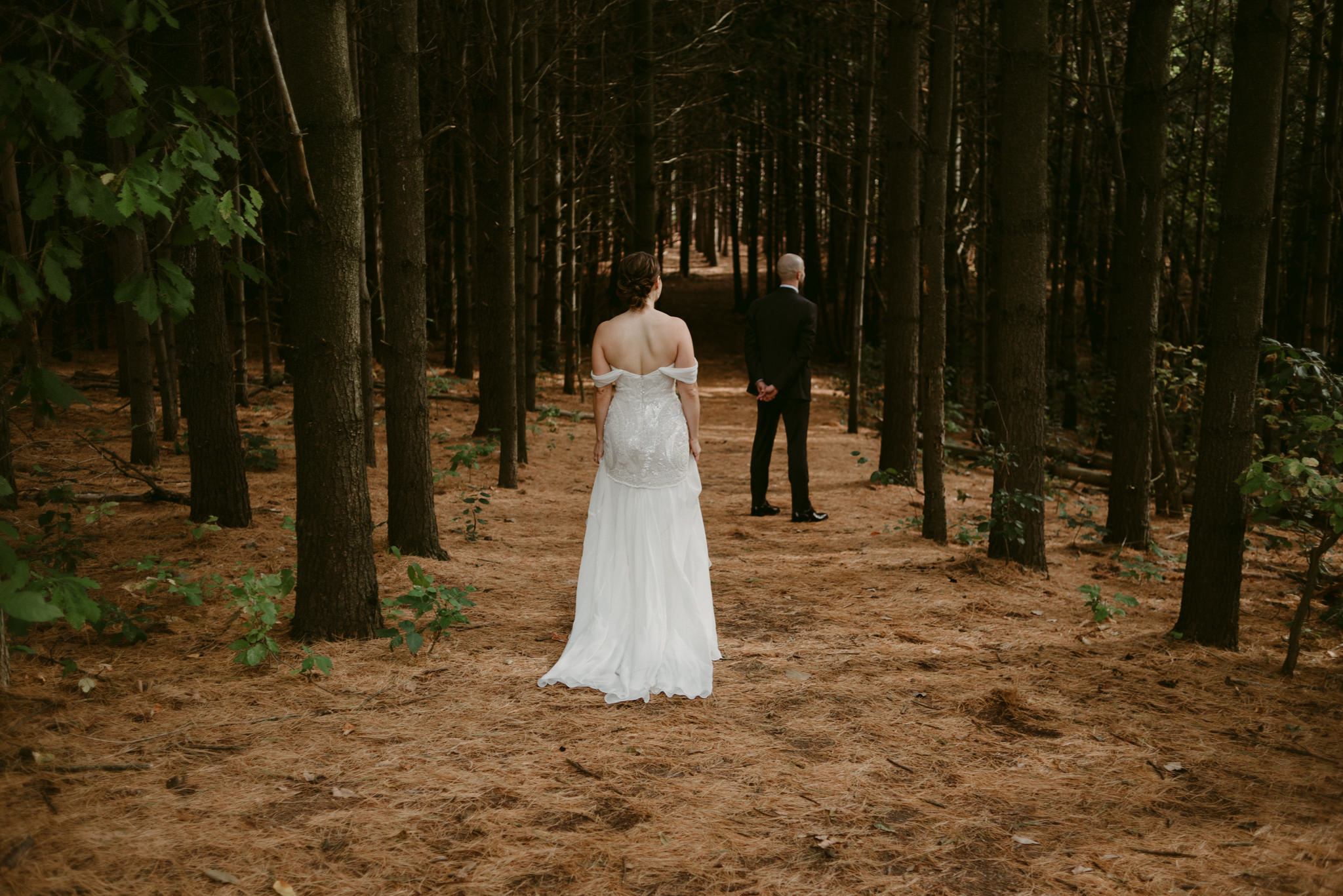 Bride walking towards groom in forest at Kortright Centre for Conservation