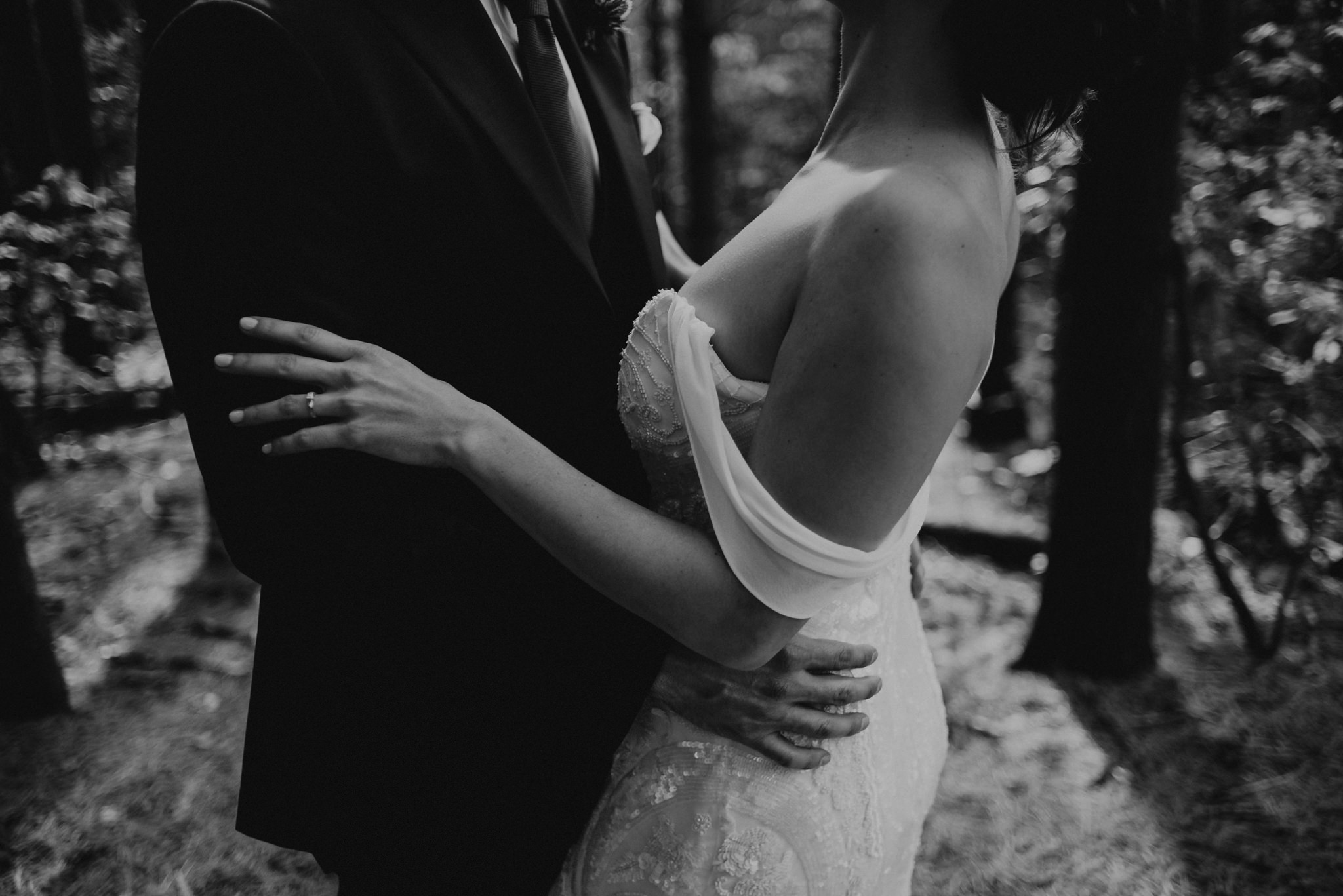Black and white images of groom hugging bride in beautiful off the shoulder wedding dress