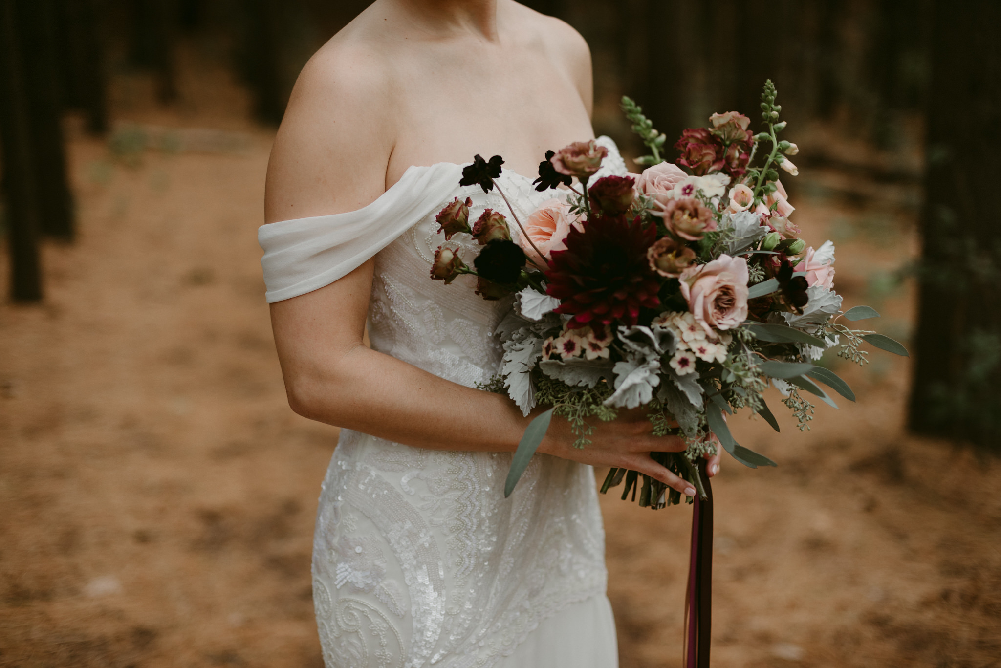 Bride holding romantic maroon and pink bouquet