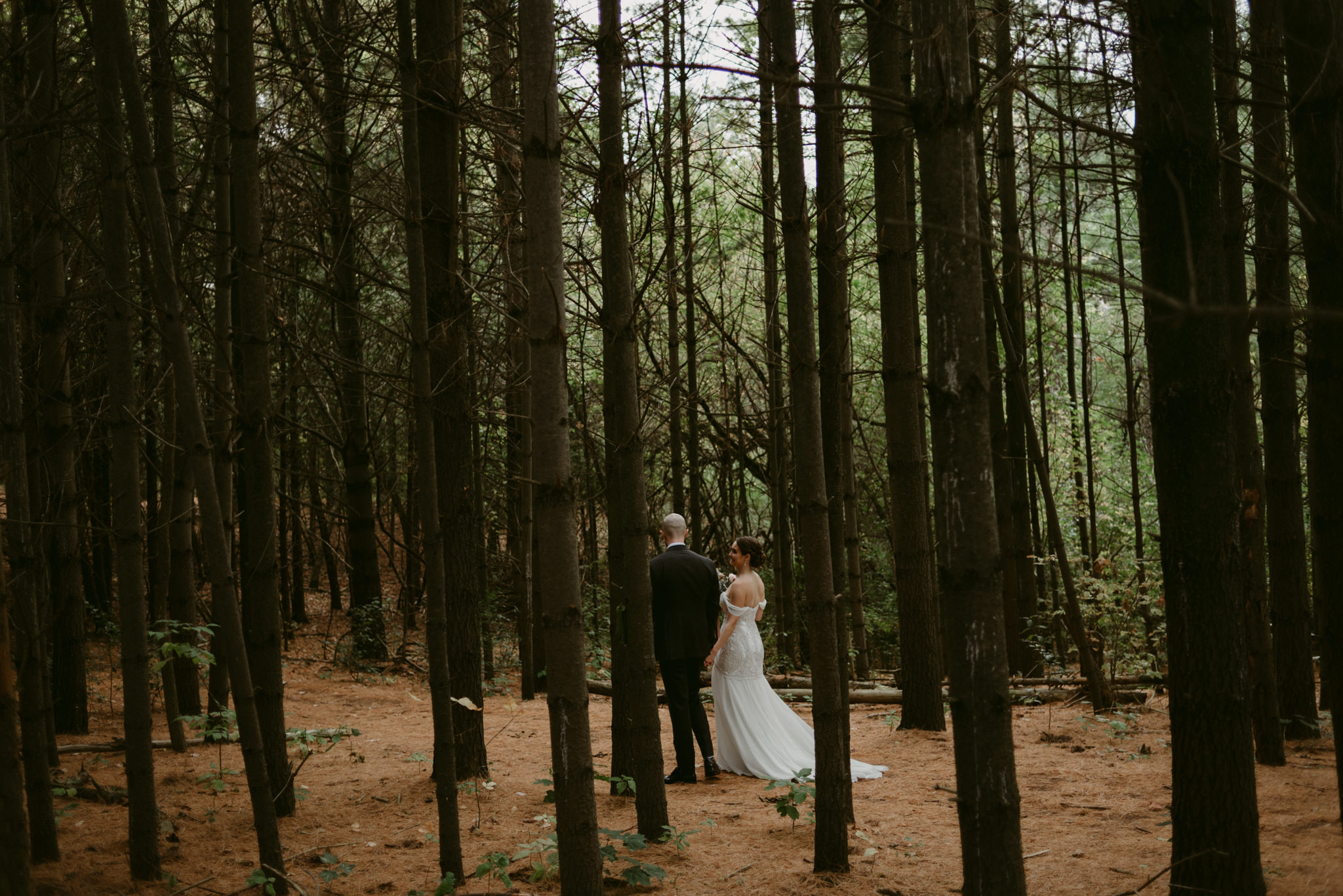 Bride and groom holding hands and walking in forest