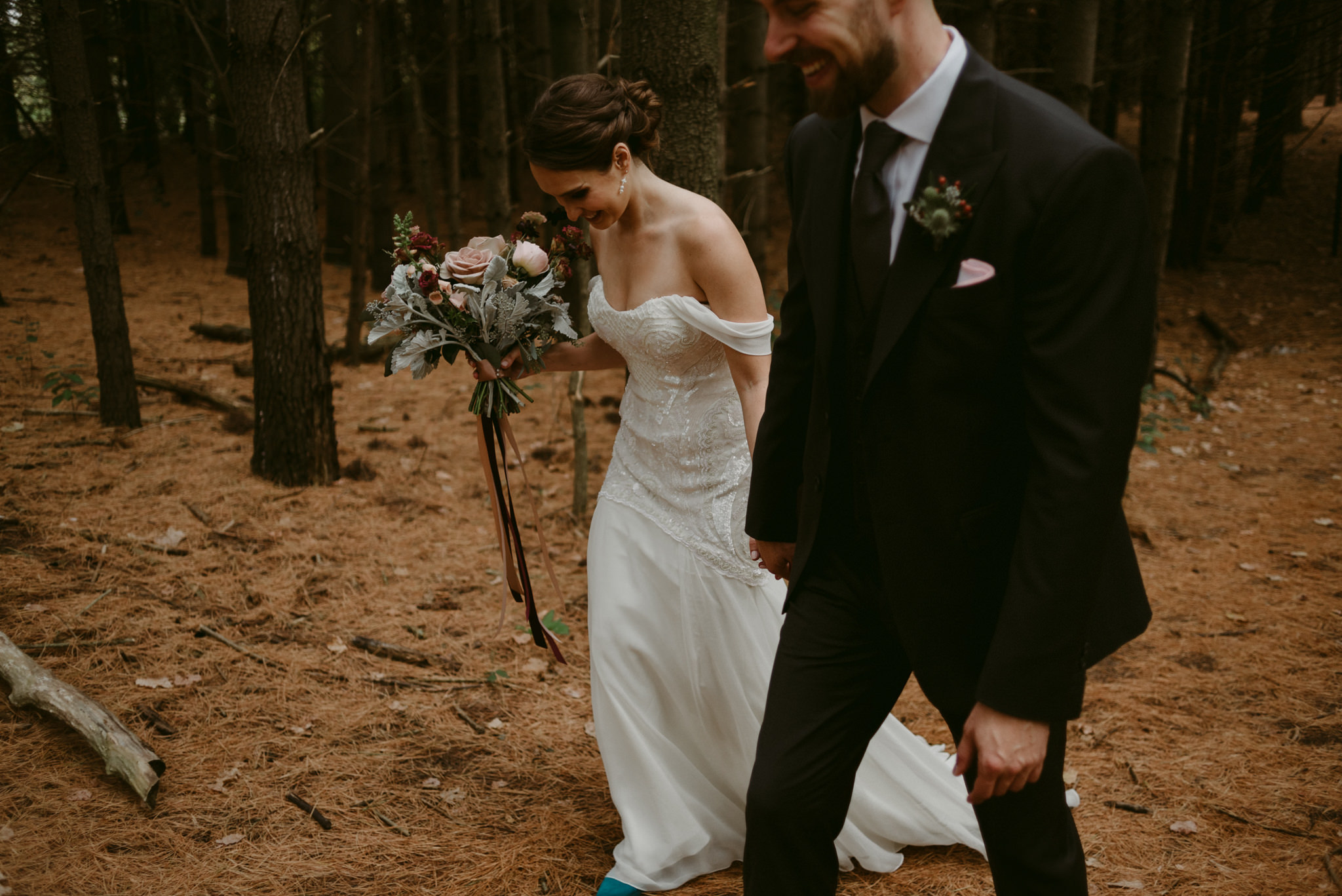 Bride and groom holding hands, laughing and walking in forest