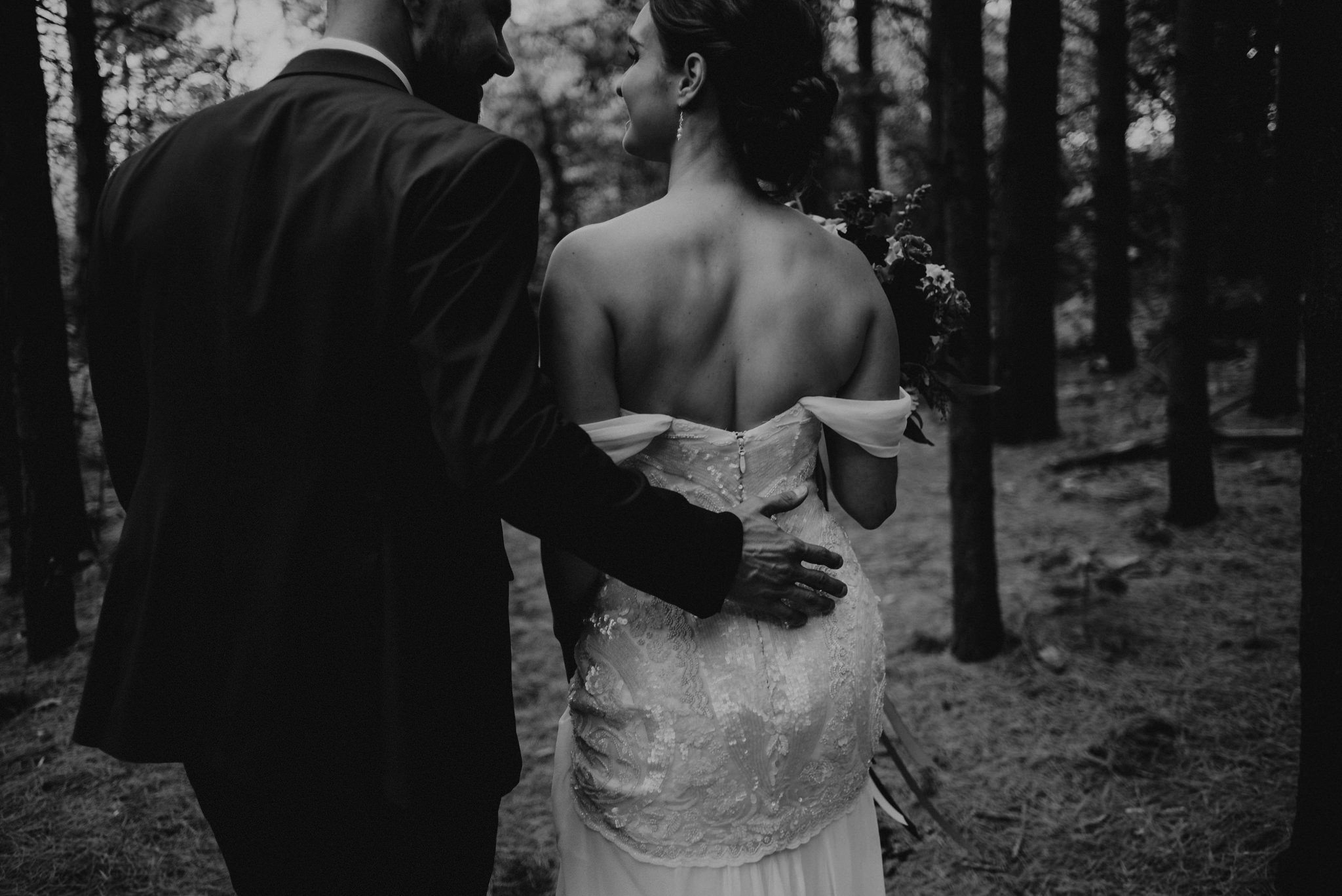 Groom's hand on back of bride's dress as they walk in forest