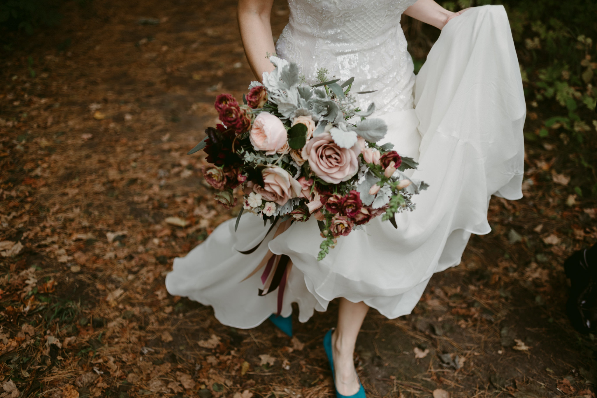 Bride in blue heels walking in forest holding bouquet