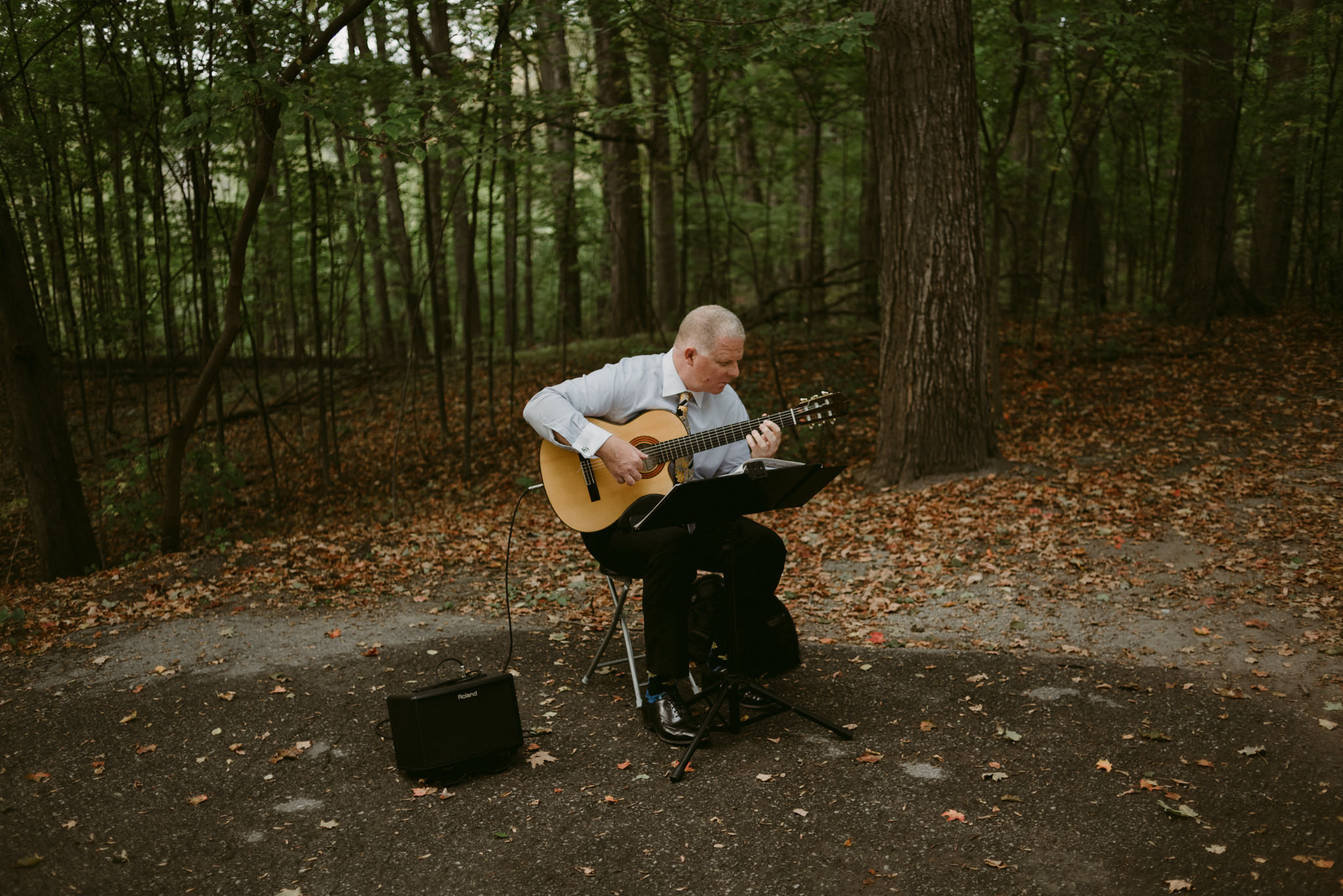 Musician playing guitar in forest before ceremony