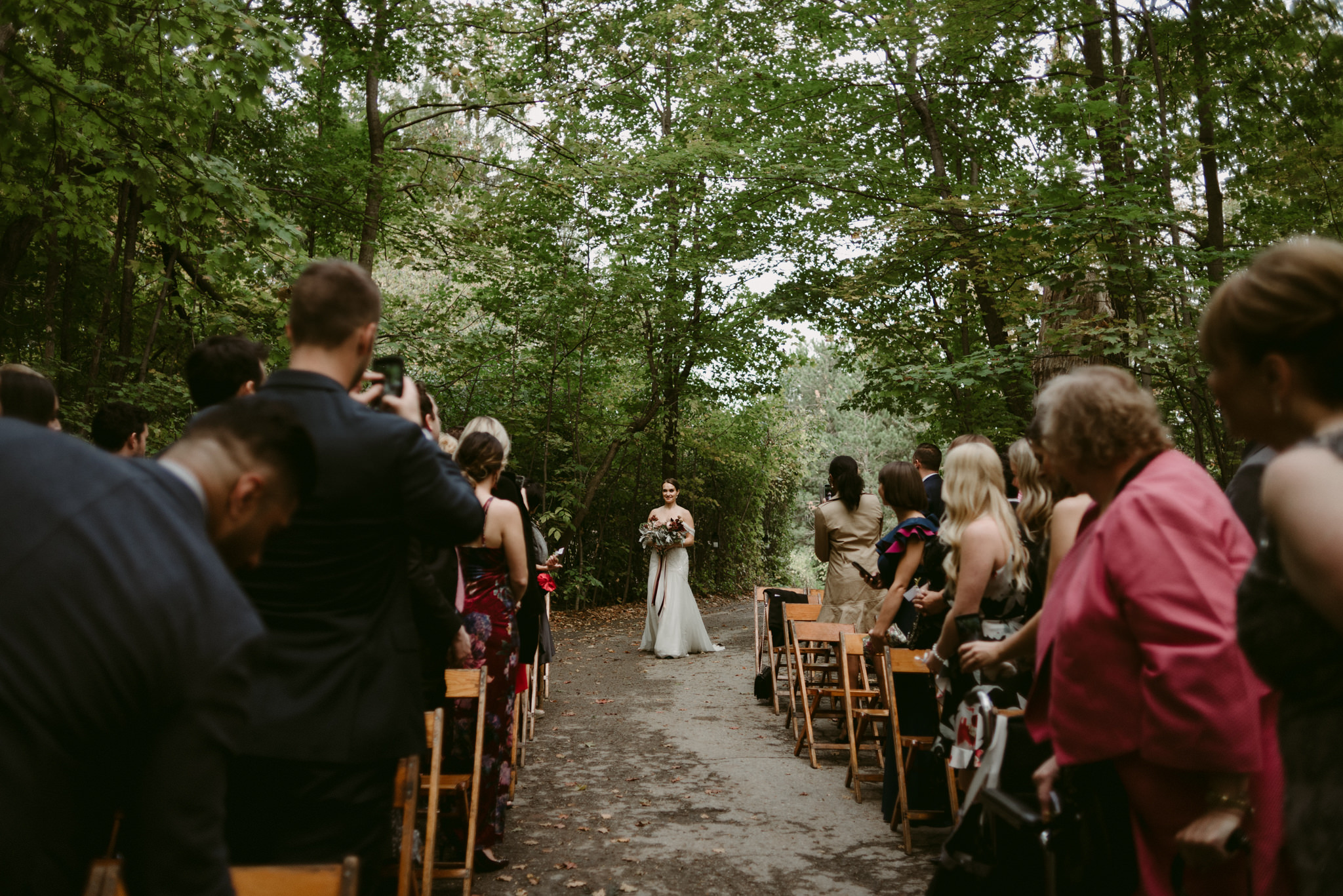 Bride walking down aisle by herself in forest wedding ceremony