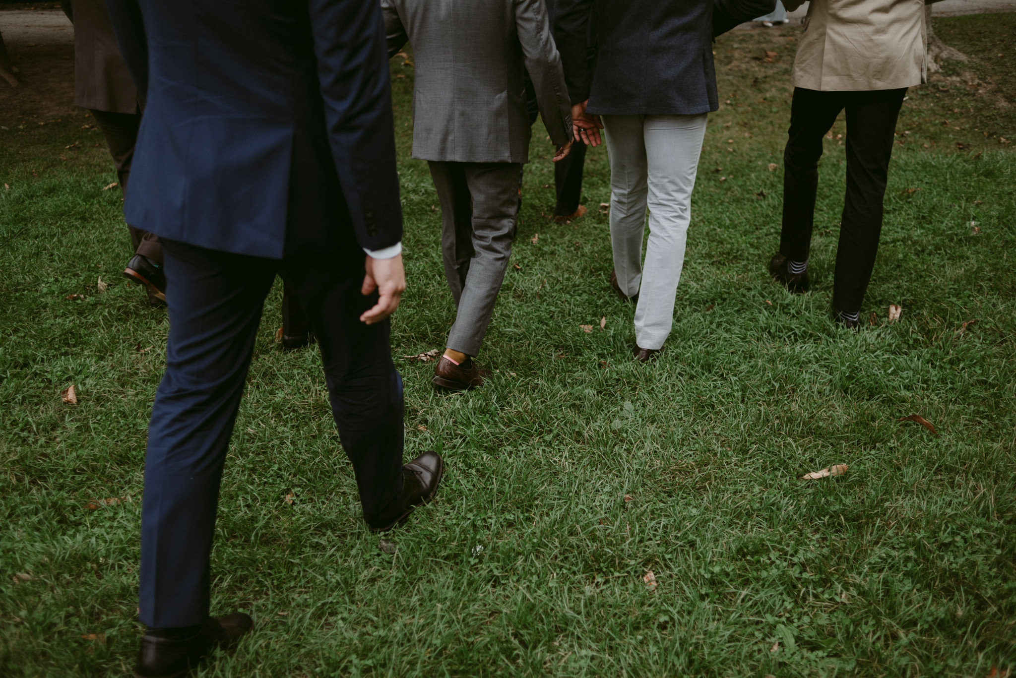 close up of groomsmen in suits walking on grass
