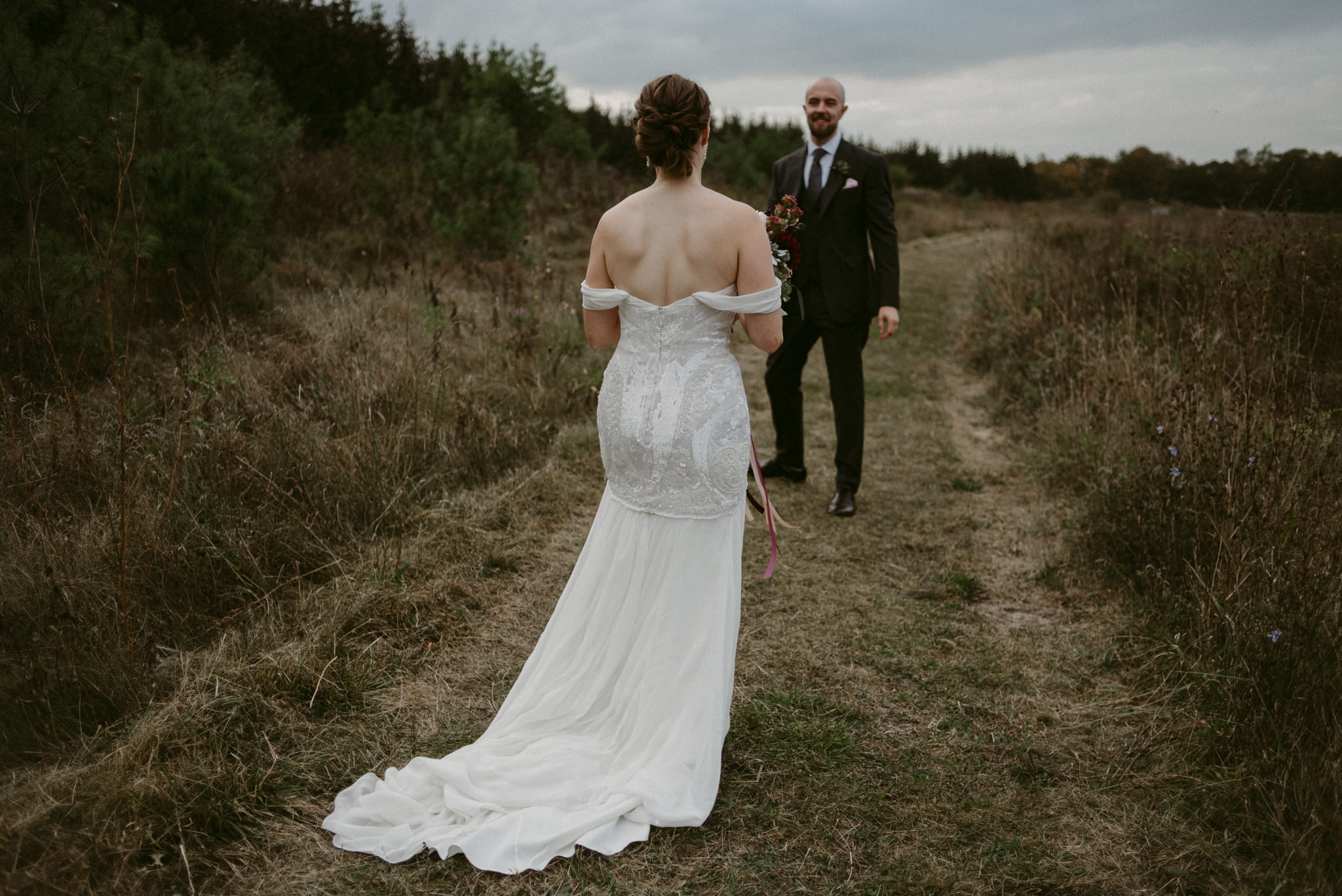 Bride walking towards groom in field