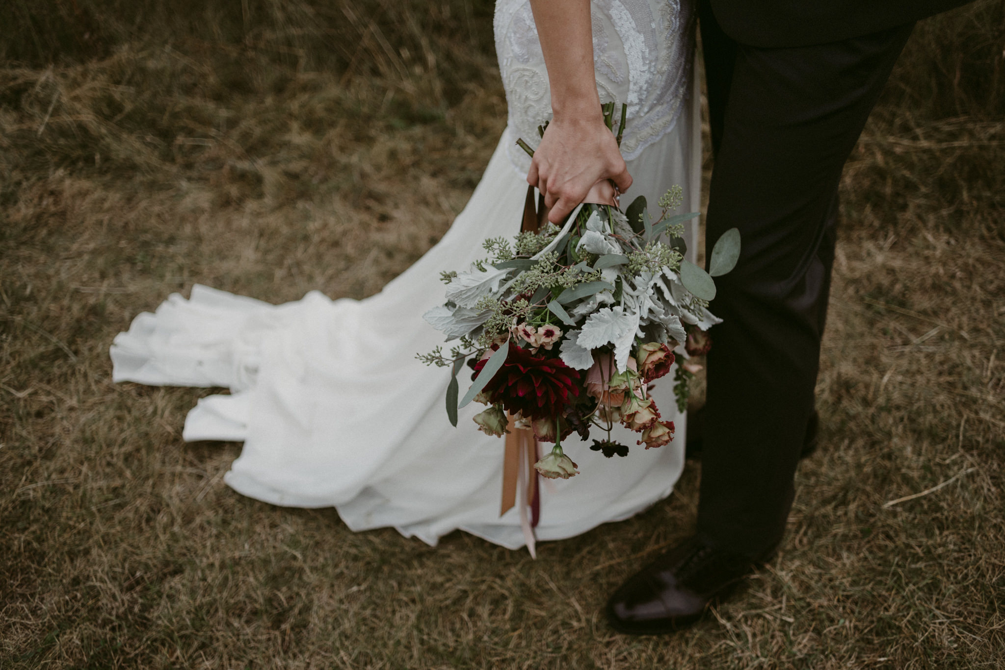 Bride holding bouquet outside in field