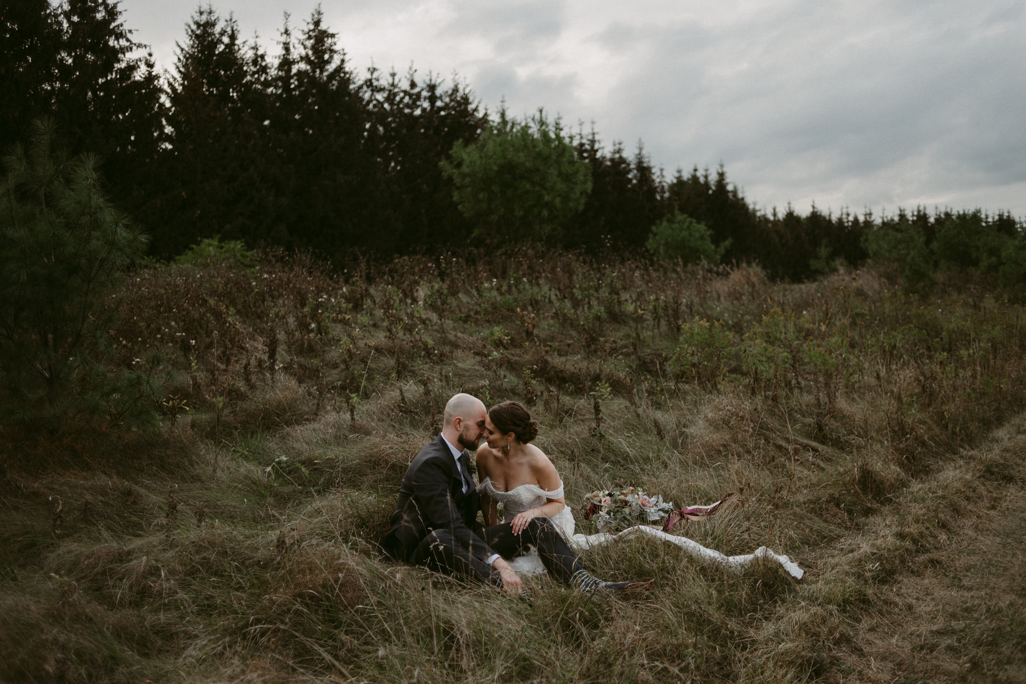 Bride and groom sitting in tall grass beside forest